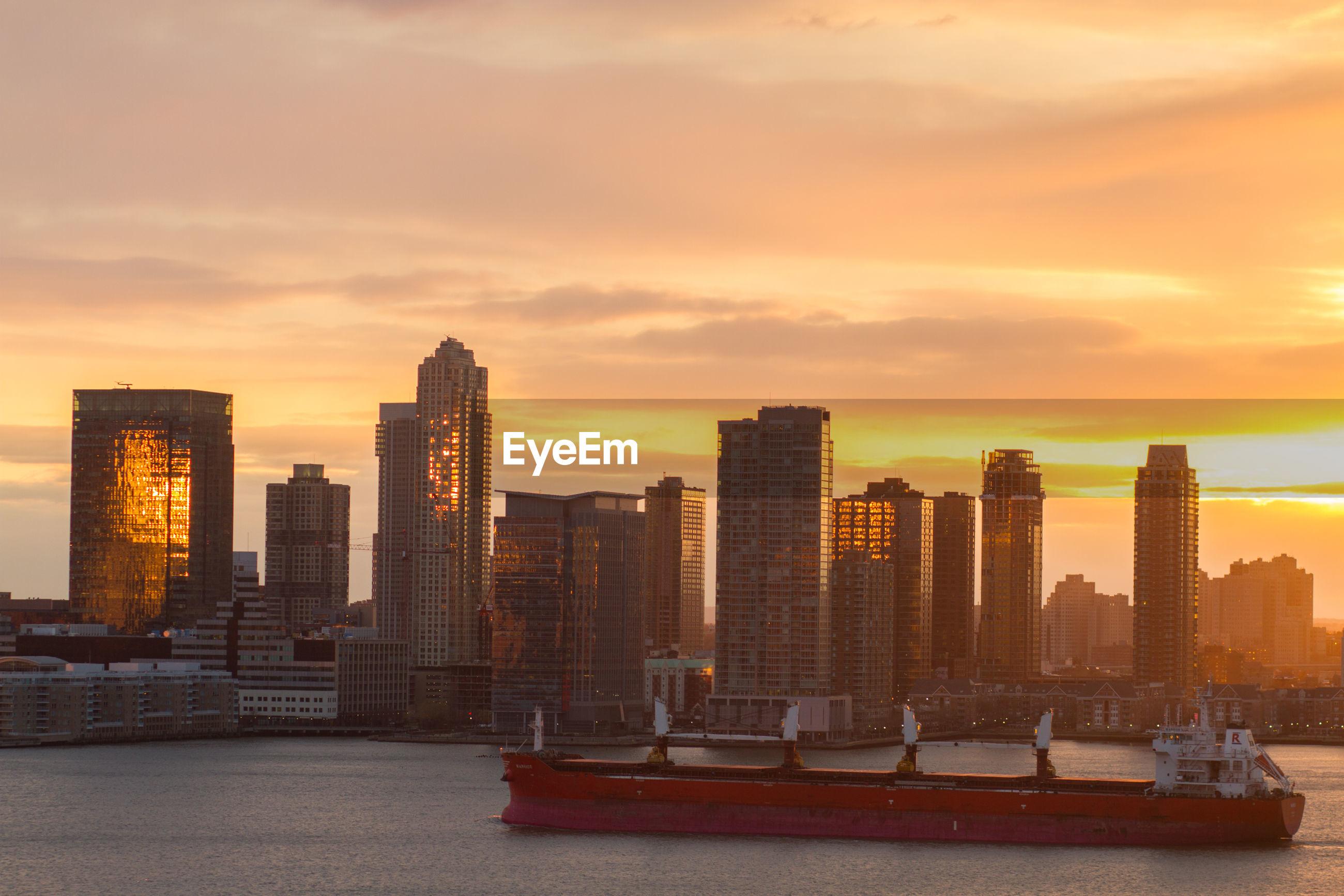 city, architecture, building exterior, sunset, skyscraper, built structure, urban skyline, cityscape, orange color, outdoors, modern, travel destinations, no people, sky, day