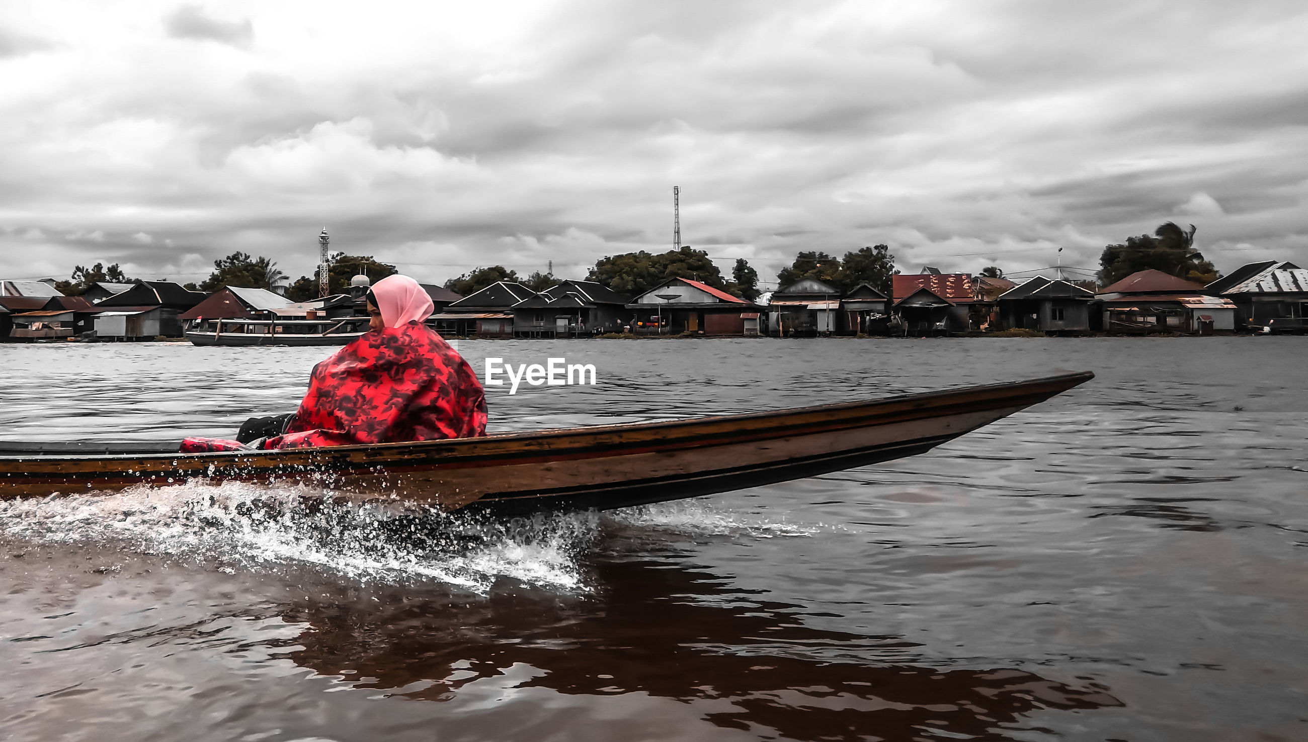 Man sailing on boat in river against sky