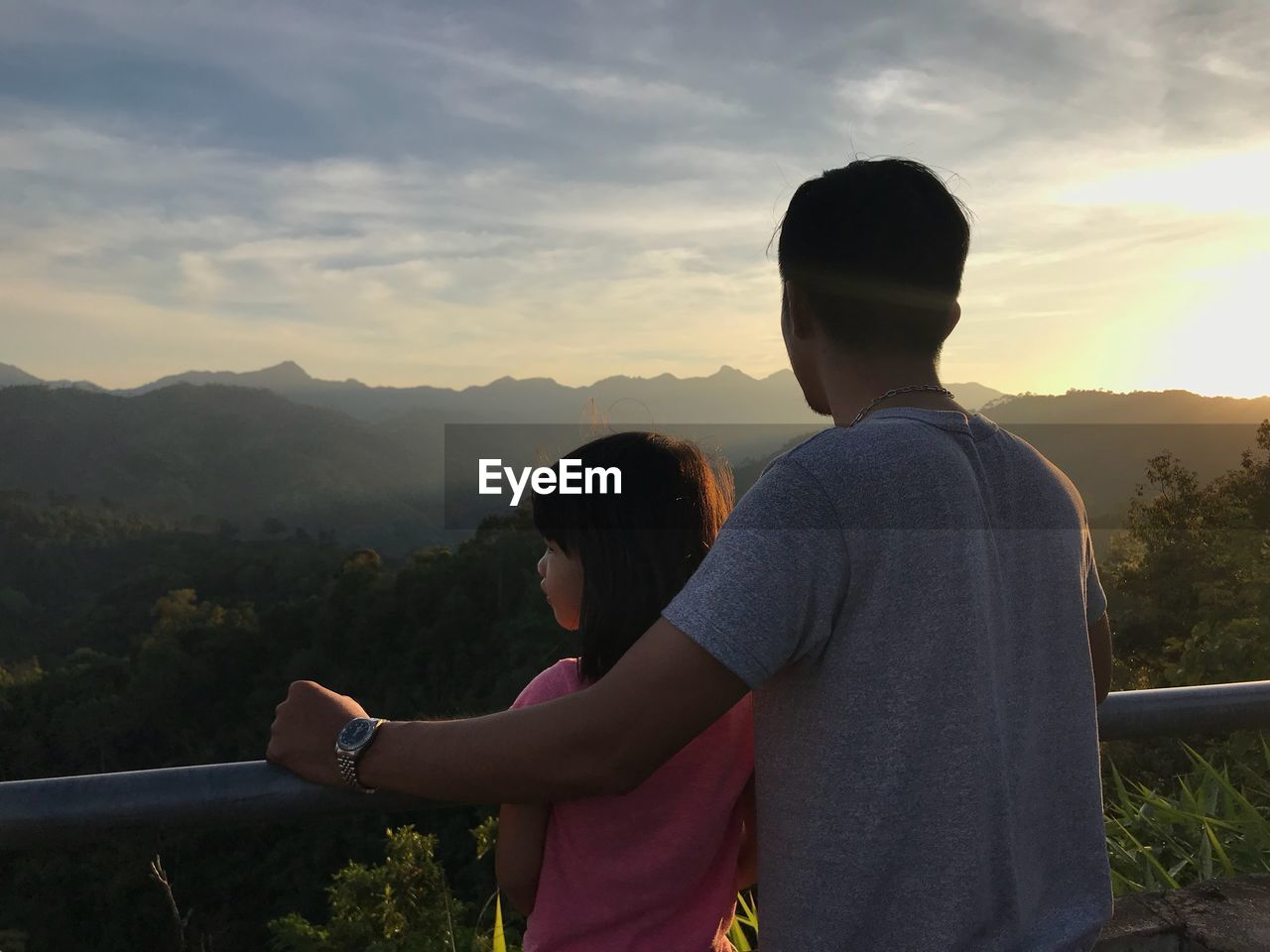 Rear view of father and daughter looking at mountains against sky during sunset