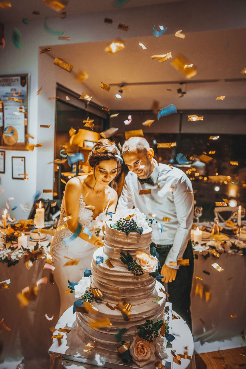 Happy Bride And Groom Standing By Wedding Cake