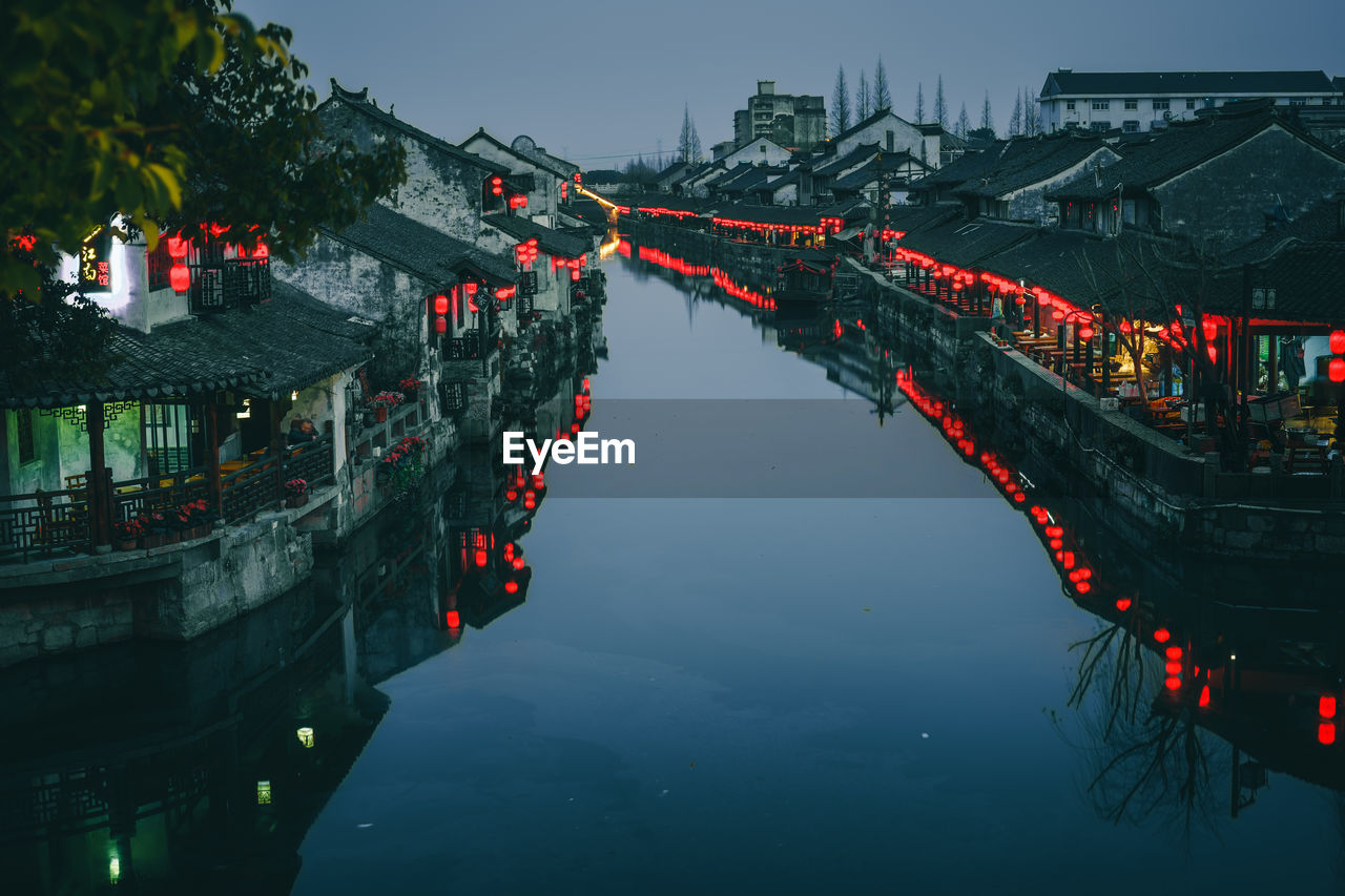 River Amidst Illuminated Houses In Town