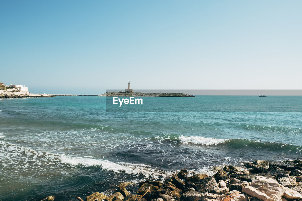 sea, water, sky, clear sky, scenics - nature, copy space, beauty in nature, rock, beach, nature, land, horizon, no people, day, horizon over water, architecture, tranquility, rock - object, solid, outdoors