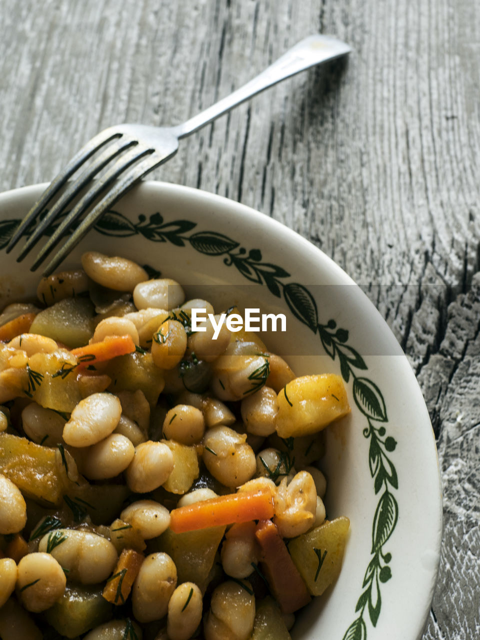 Close-up of baked beans in bowl on wooden table