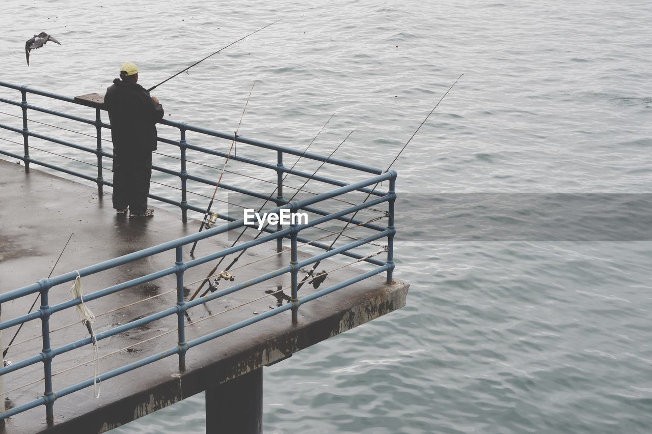 High Angle View Of Man Fishing At Santa Monica Pier Over Sea