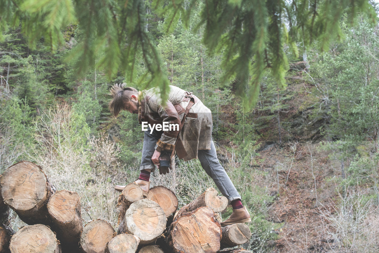 Side View Of Young Man Standing On Logs In Forest