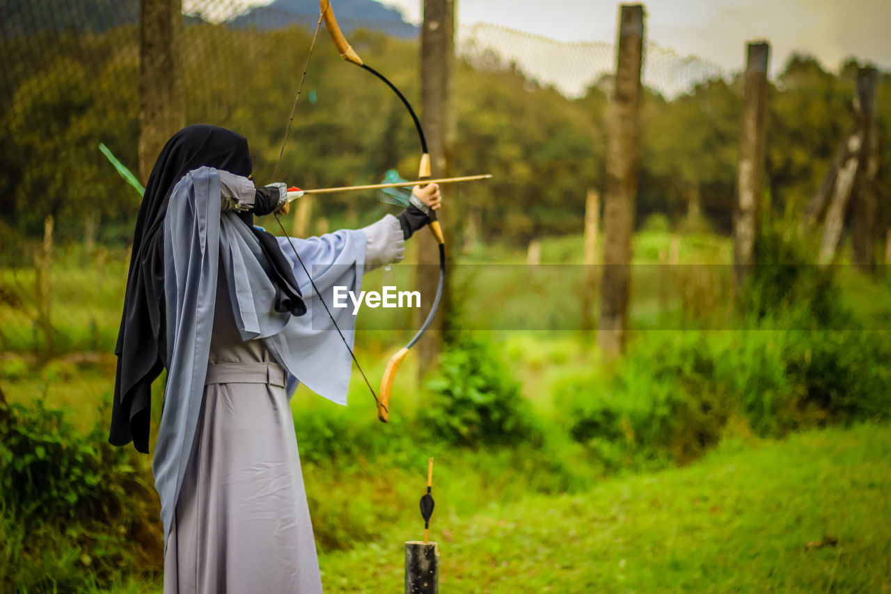 plant, one person, land, holding, tree, focus on foreground, three quarter length, real people, nature, field, lifestyles, arrow - bow and arrow, standing, grass, day, leisure activity, adult, archery, clothing, outdoors, hairstyle