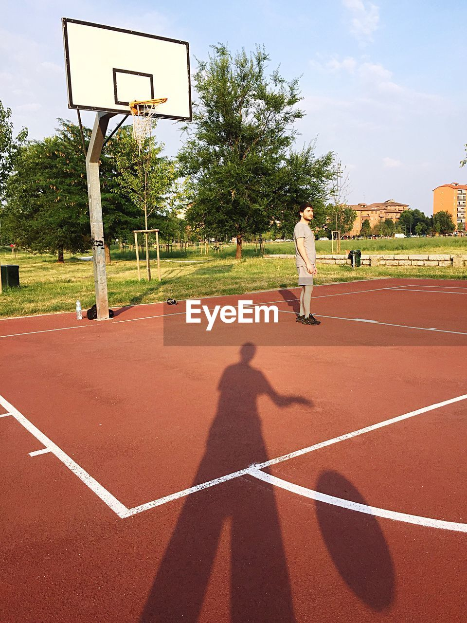 Side View Of Man Standing In Basketball Court
