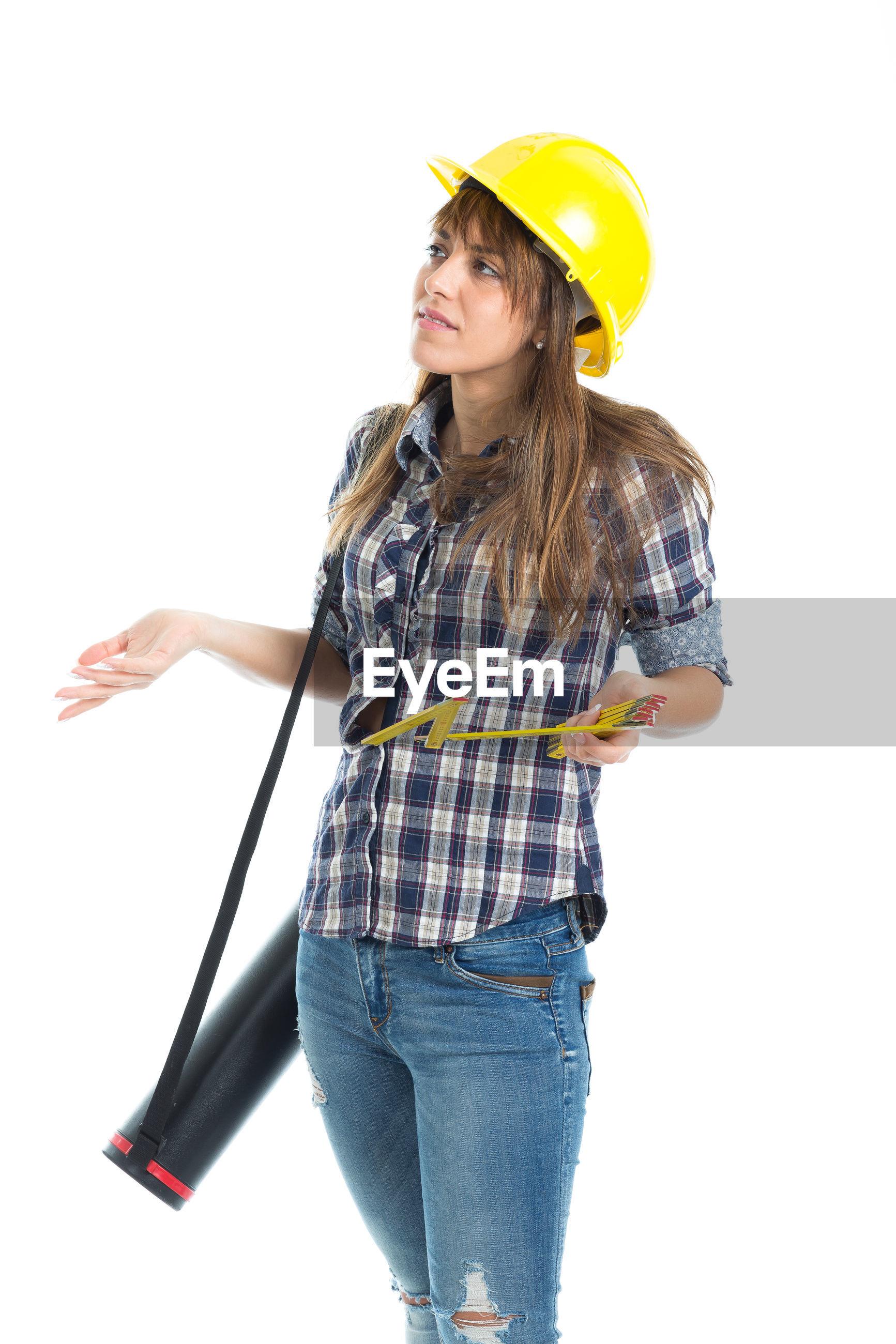 Female engineer standing against white background
