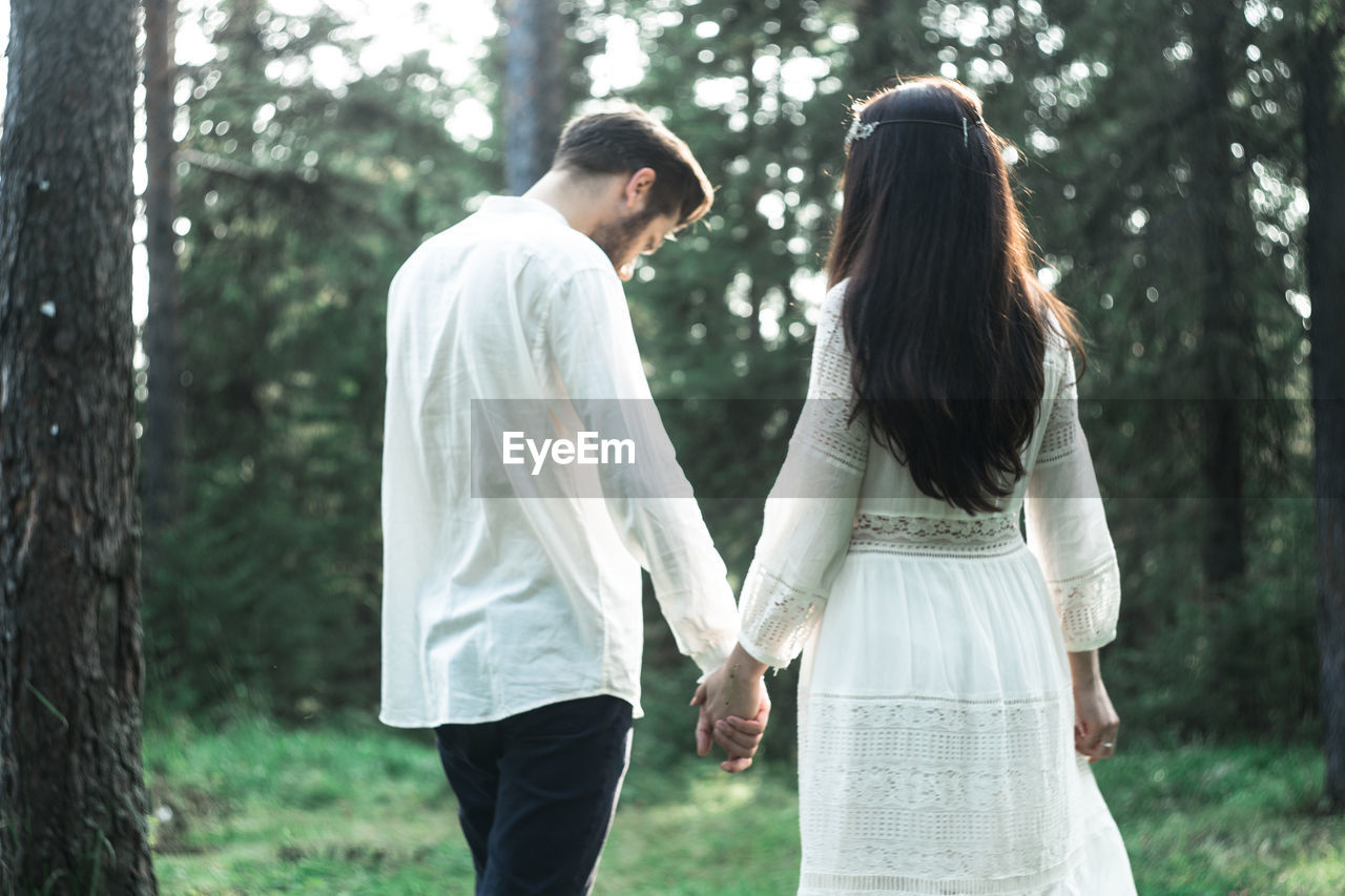 two people, tree, togetherness, three quarter length, women, casual clothing, couple - relationship, standing, love, plant, bonding, forest, men, land, leisure activity, heterosexual couple, adult, young adult, real people, positive emotion, outdoors, hairstyle, woodland