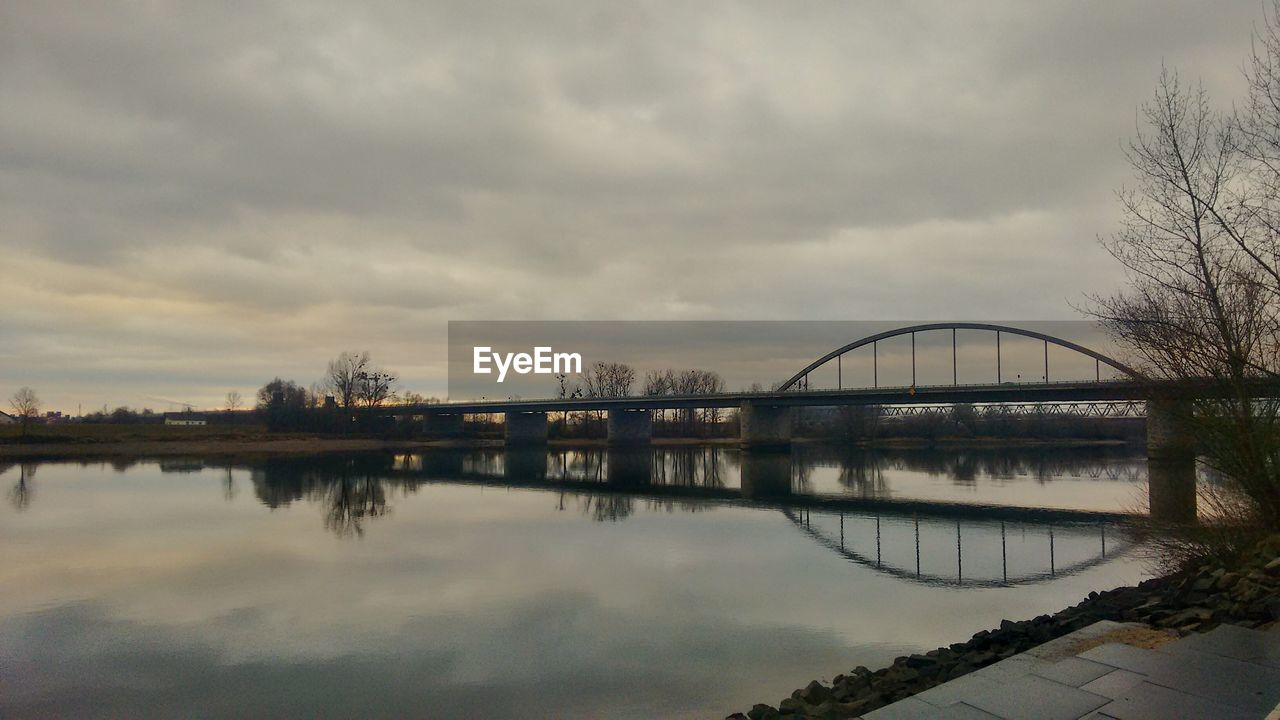 reflection, sky, water, bridge - man made structure, cloud - sky, architecture, built structure, connection, tree, outdoors, no people, bare tree, nature, day, building exterior, beauty in nature