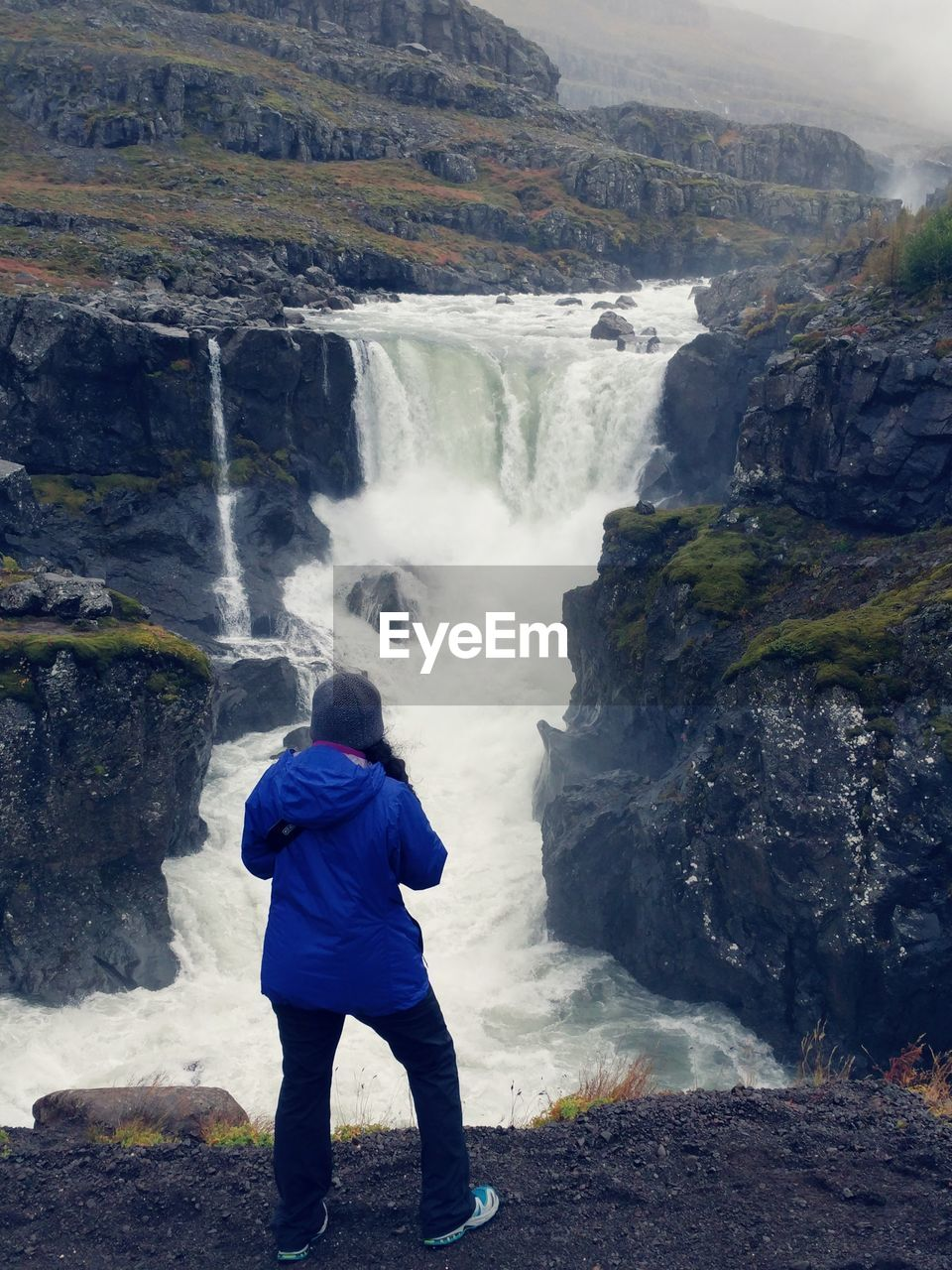 rear view, real people, waterfall, one person, water, scenics - nature, beauty in nature, leisure activity, long exposure, rock, lifestyles, motion, standing, rock - object, solid, nature, flowing water, land, outdoors, power in nature, looking at view