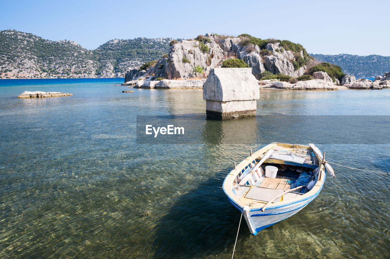 Boat moored on sea against mountain