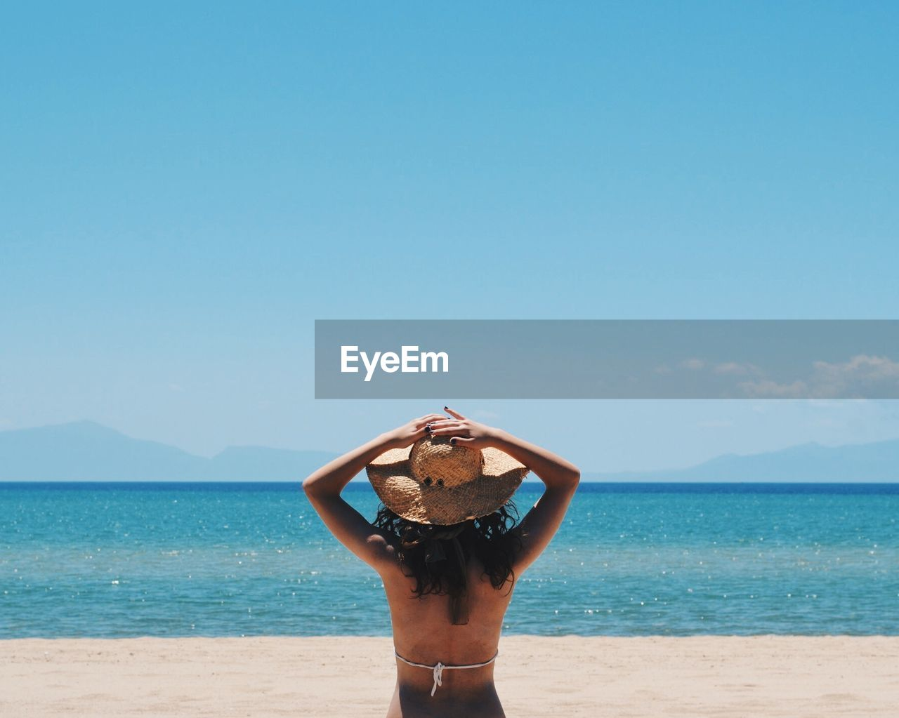 Rear View Of Young Woman Wearing Sun Hat On Beach Against Clear Sky