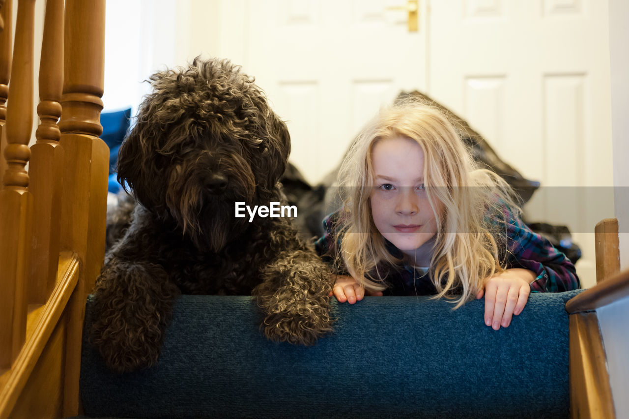 Portrait of girl with dog lying at home