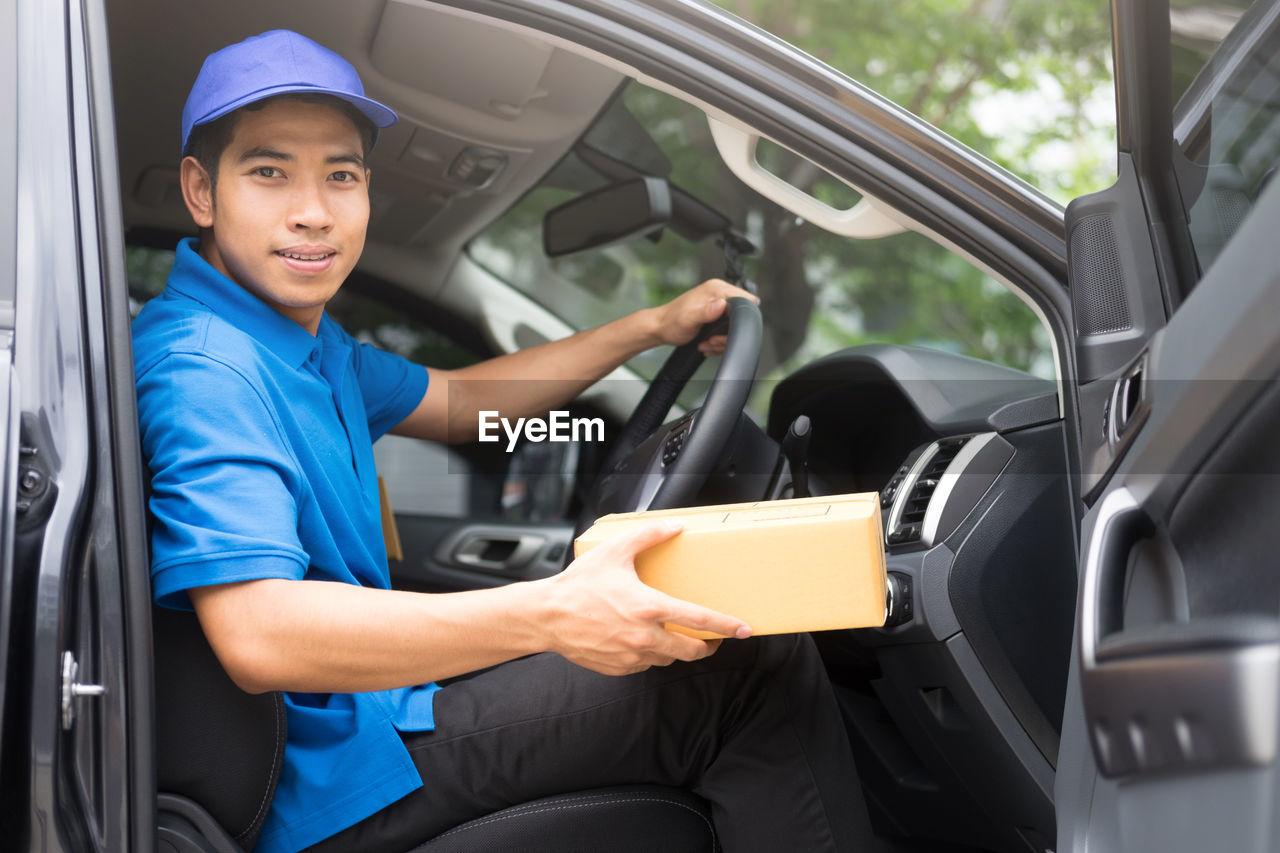 Portrait of male worker delivering package in delivery van