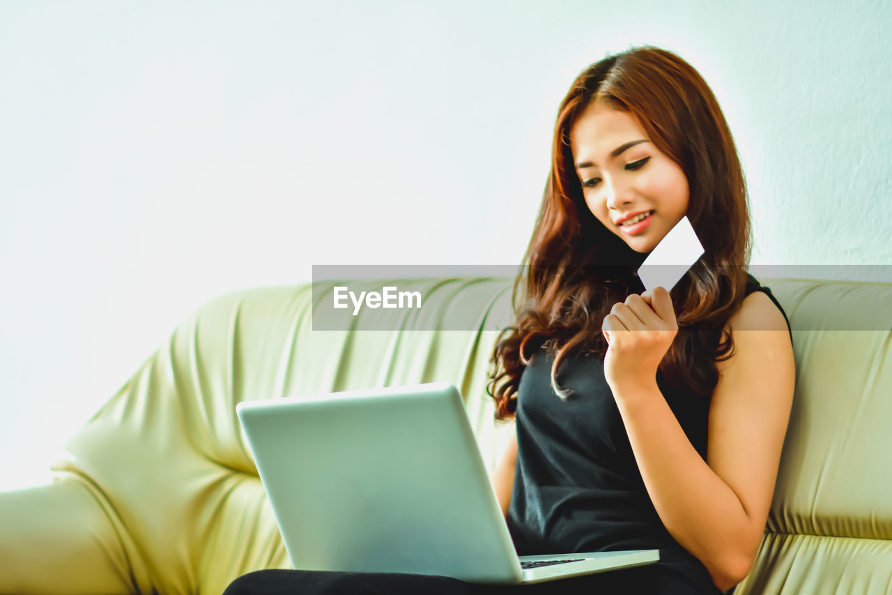 wireless technology, communication, technology, connection, one person, young adult, front view, computer, indoors, young women, holding, adult, laptop, portable information device, women, portability, using laptop, real people, beautiful woman, hairstyle, surfing the net