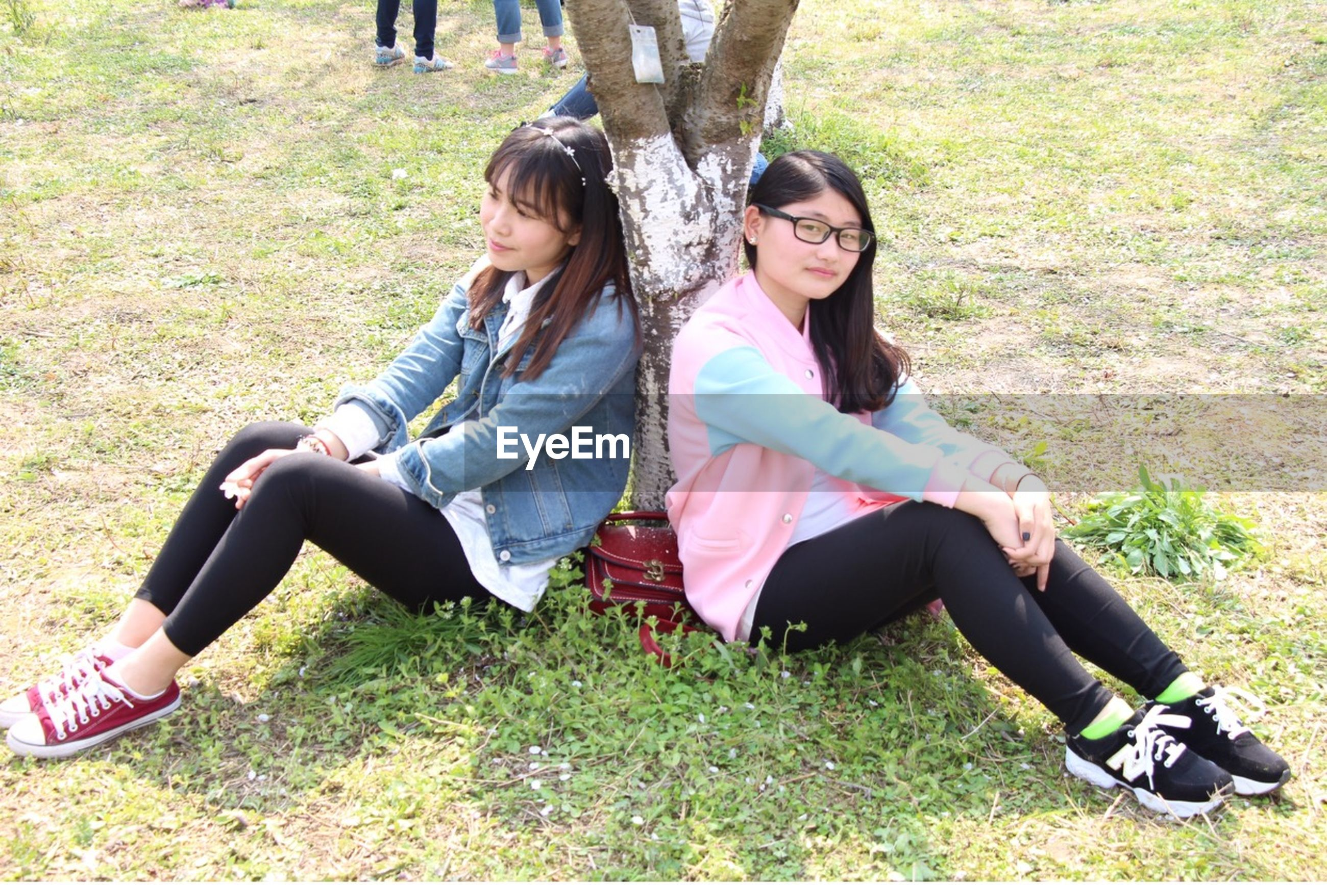 grass, lifestyles, leisure activity, person, casual clothing, young adult, sitting, full length, relaxation, young women, togetherness, park - man made space, smiling, happiness, field, lying down, childhood