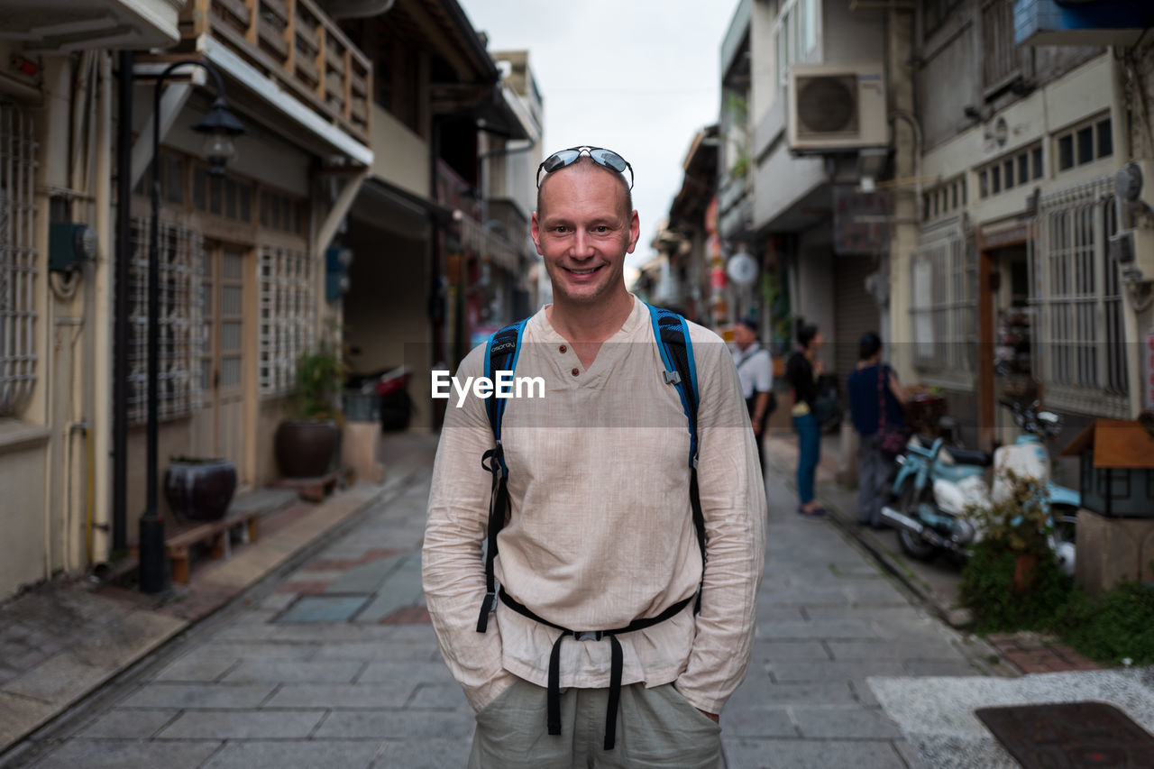 looking at camera, portrait, smiling, architecture, one person, focus on foreground, standing, front view, city, building exterior, happiness, casual clothing, built structure, emotion, real people, three quarter length, incidental people, street, outdoors, alley