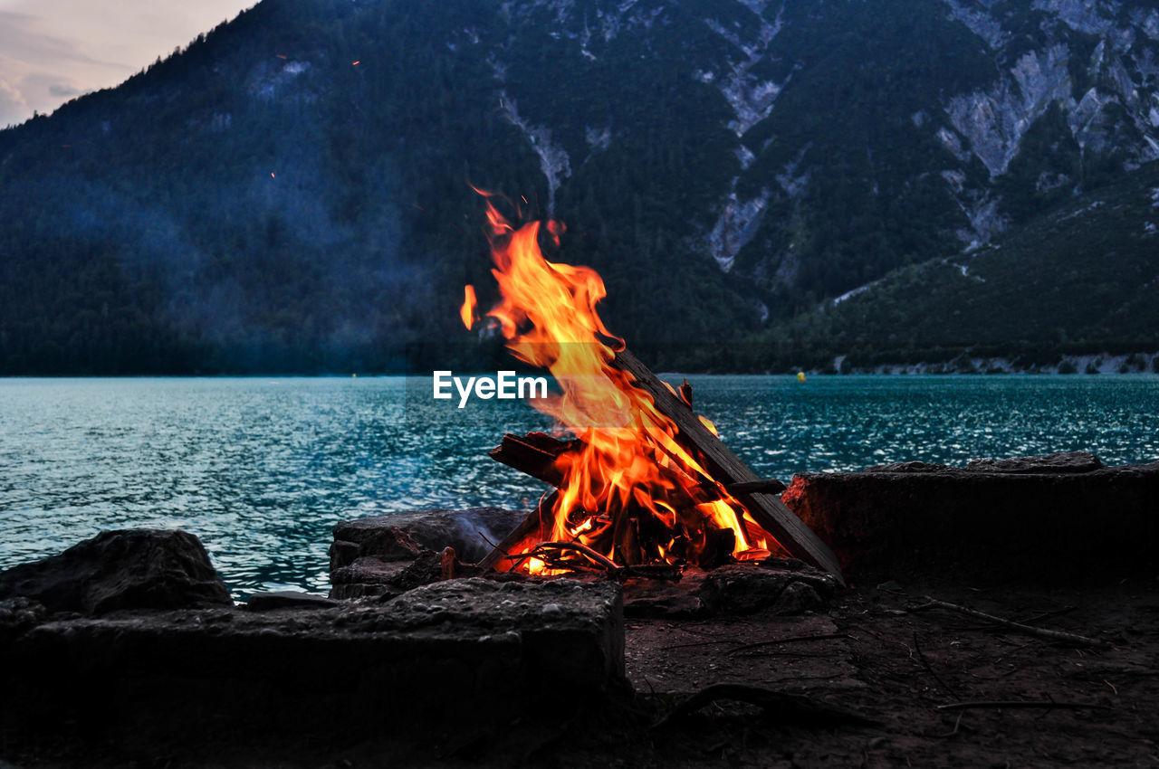 Bonfire Against Lake And Mountain