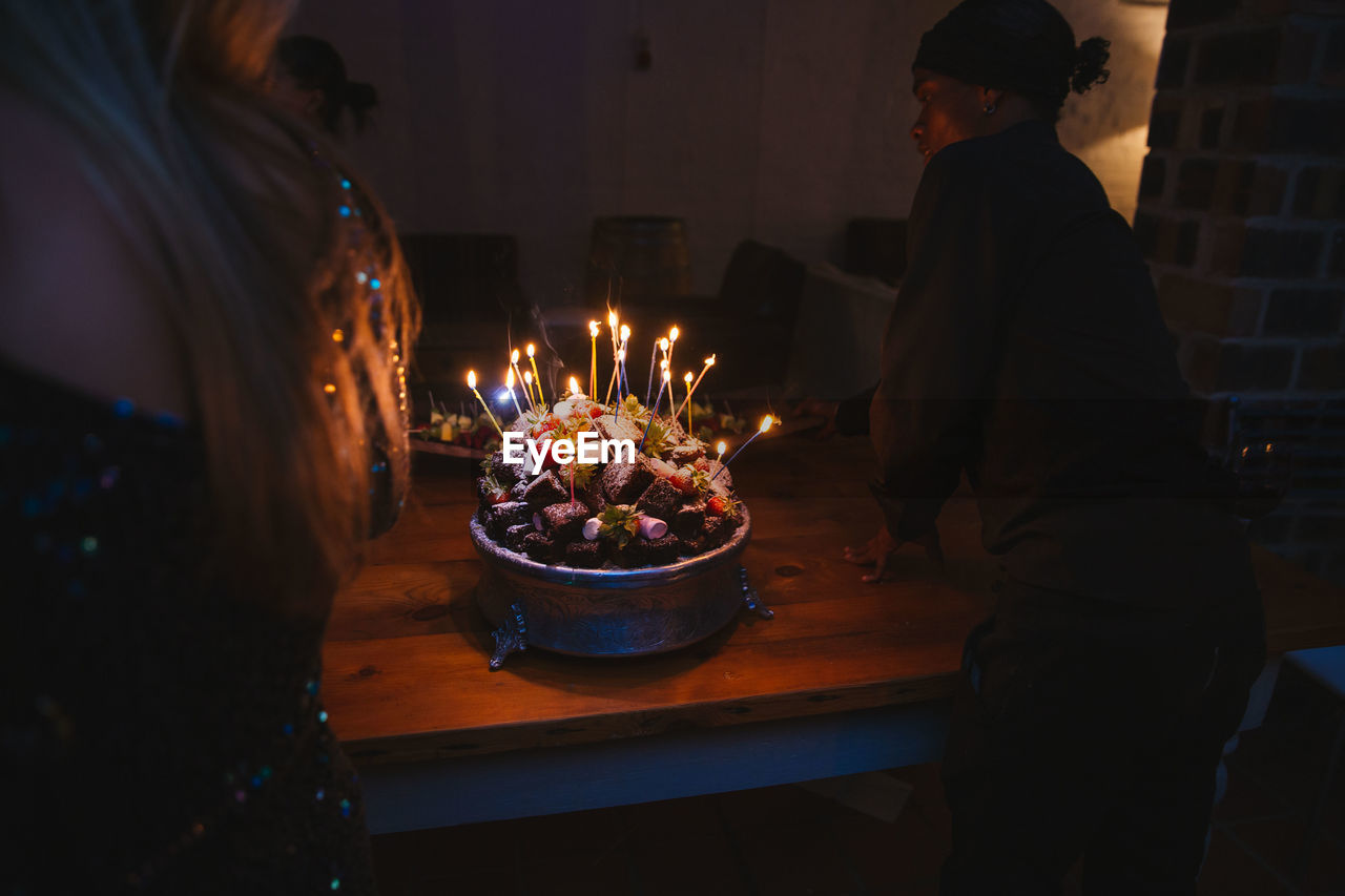 burning, fire, candle, flame, real people, fire - natural phenomenon, food and drink, indoors, heat - temperature, women, table, celebration, men, food, lifestyles, adult, glowing, illuminated, togetherness, event, birthday candles