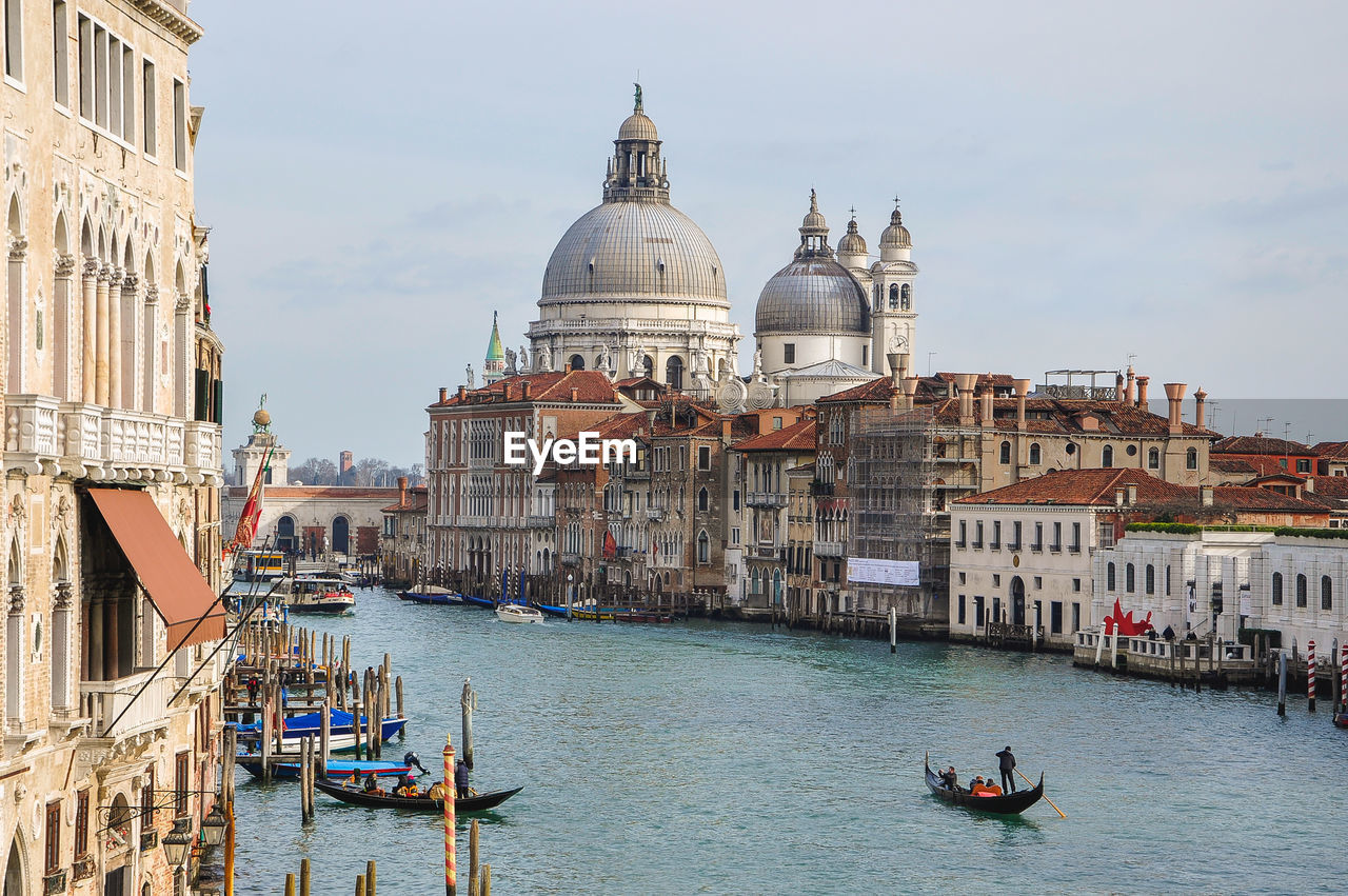 architecture, building exterior, dome, religion, place of worship, spirituality, built structure, canal, nautical vessel, gondola, transportation, outdoors, travel destinations, water, tourism, day, real people, gondola - traditional boat, past, sky, city