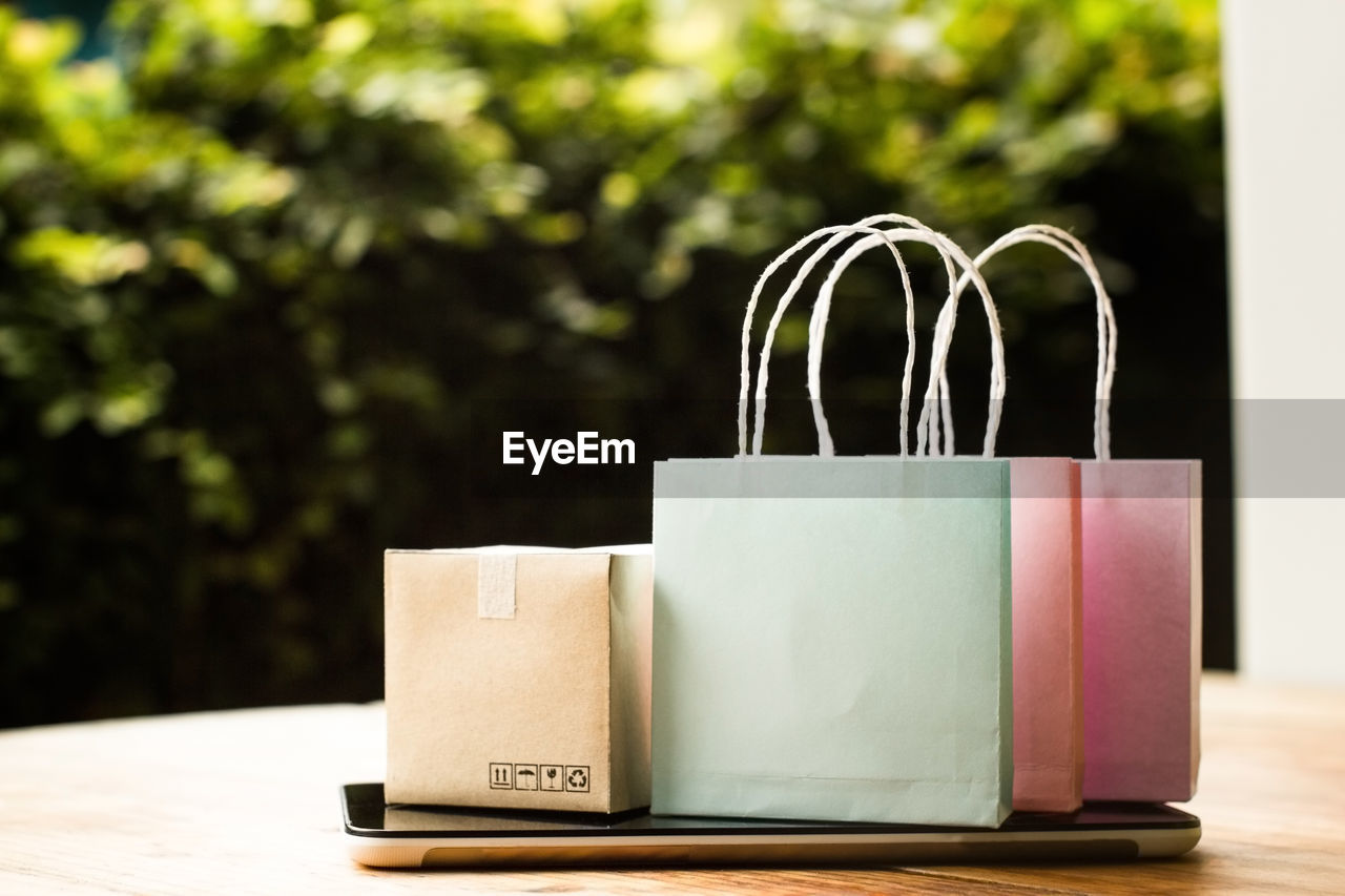 Close-up of shopping bags on smart phone at table