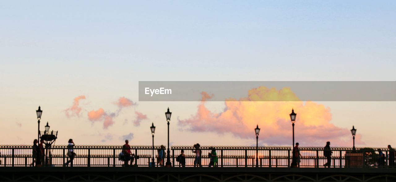 railing, sunset, water, architecture, built structure, sky, building exterior, outdoors, sea, clear sky, silhouette, travel destinations, real people, nature, day, beauty in nature, city