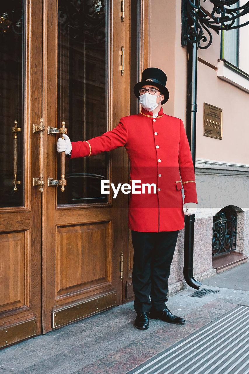 FULL LENGTH PORTRAIT OF MAN STANDING ON DOOR