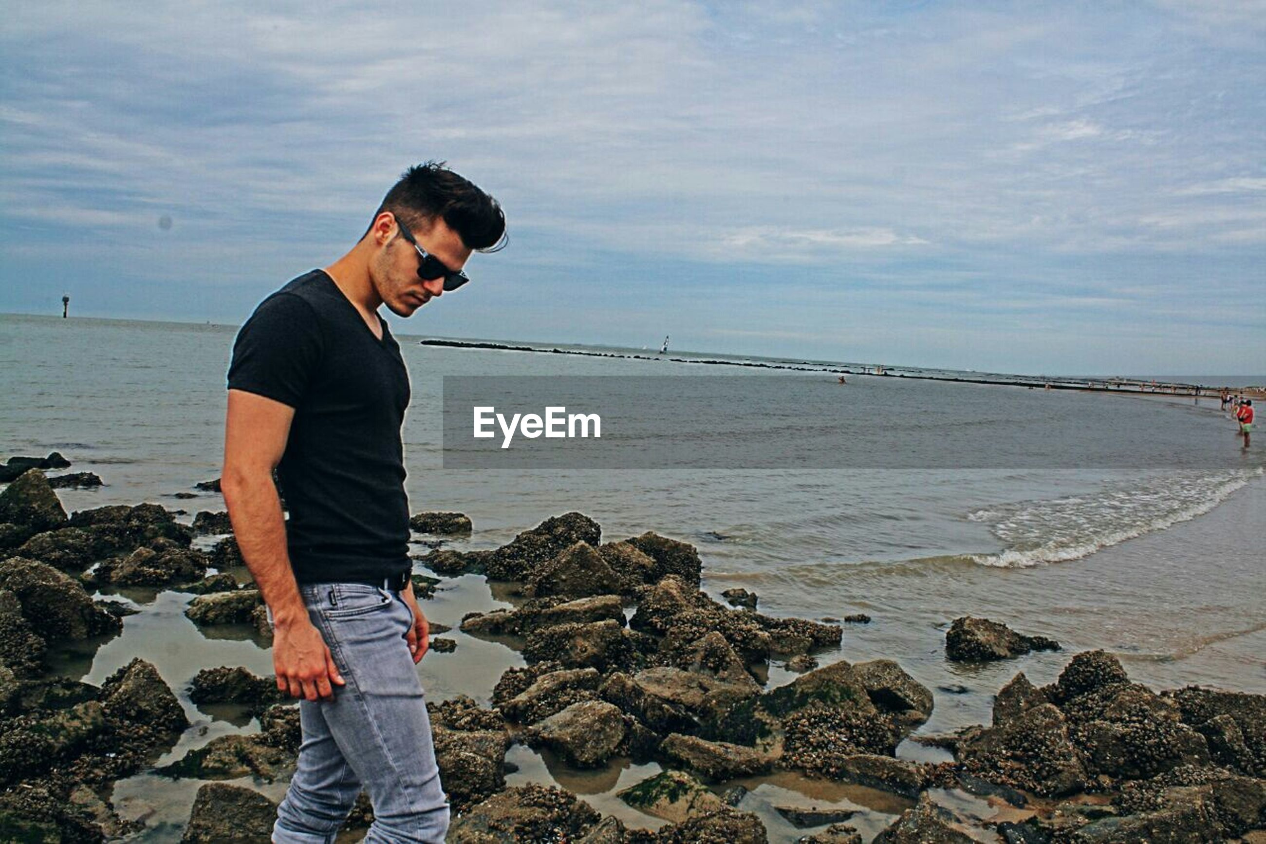 Handsome man wearing sunglasses standing at sea shore against sky