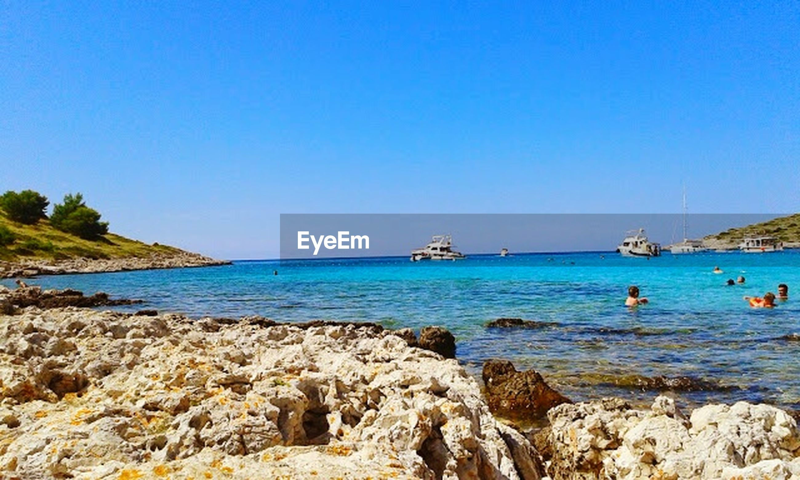 sea, water, clear sky, blue, nautical vessel, copy space, transportation, horizon over water, scenics, tranquility, tranquil scene, mode of transport, beauty in nature, rock - object, beach, nature, boat, shore, rock formation, day