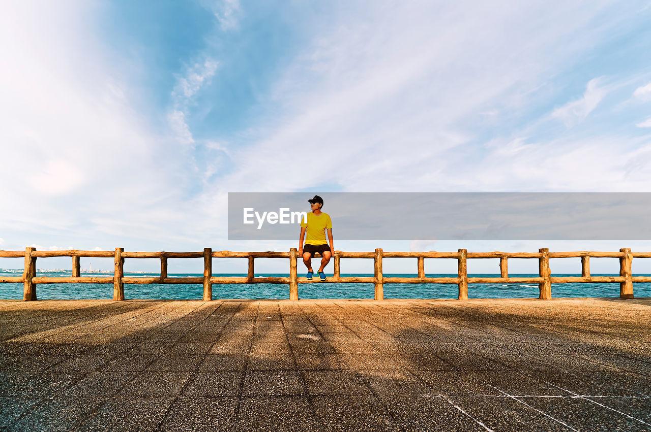Man Sitting On Railing At Promenade Against Cloudy Sky