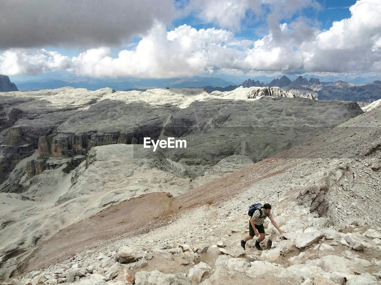 High angle view of man hiking on mountains against cloudy sky