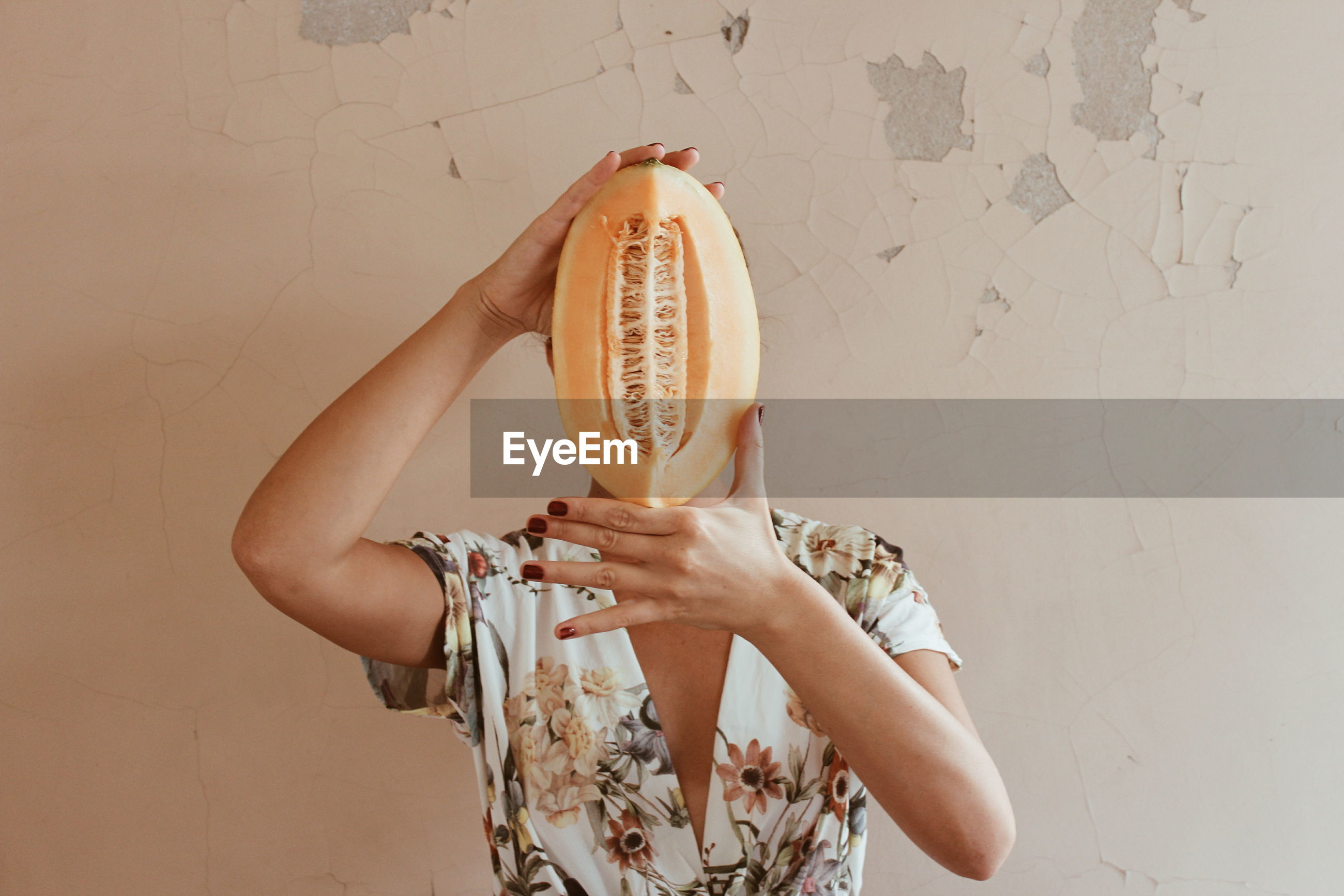 Woman covering face with sliced vegetable against wall at home