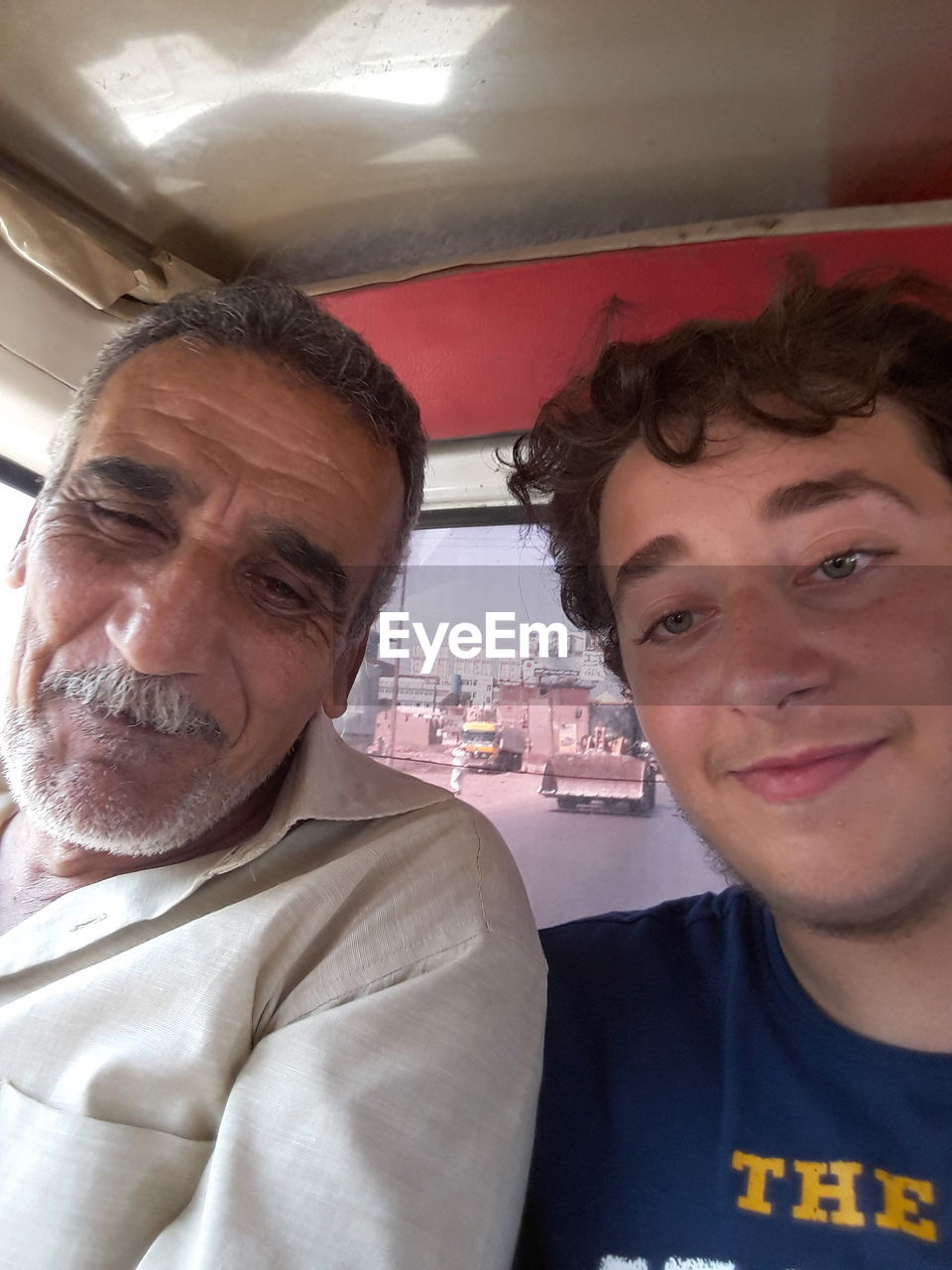 Portrait Of Smiling Young Man Sitting With Senior Man In Vehicle