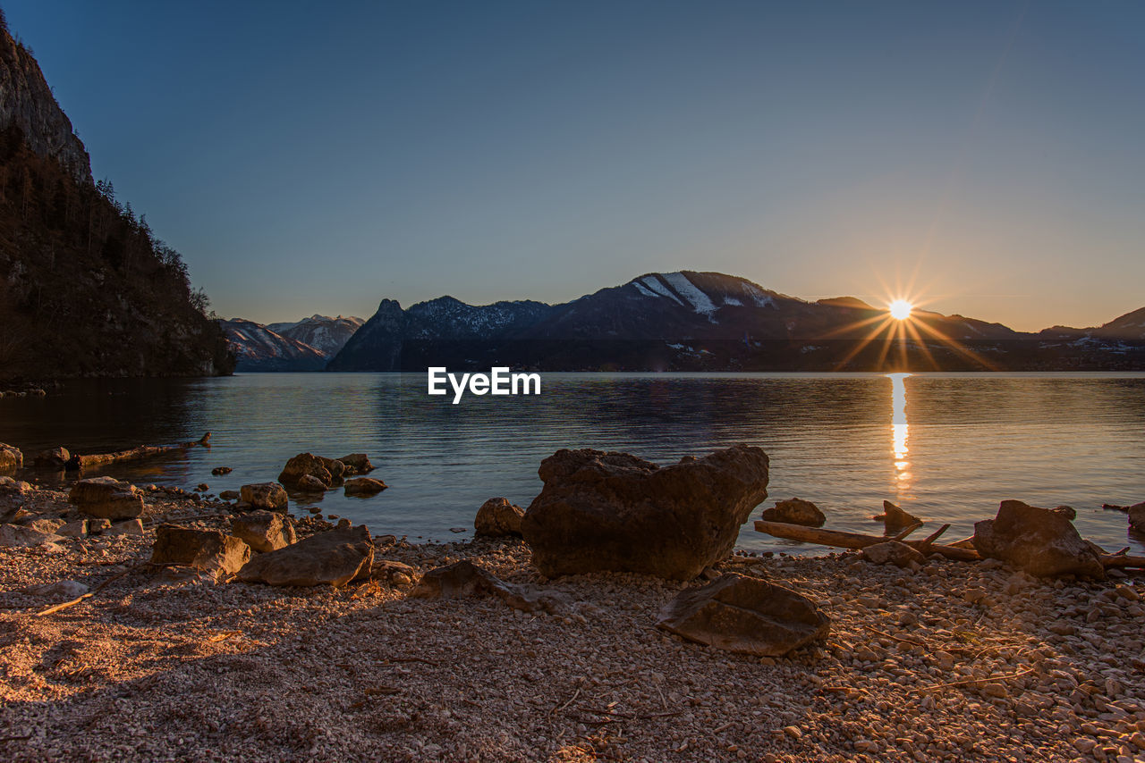 sky, water, beauty in nature, rock, scenics - nature, tranquility, sunset, solid, tranquil scene, rock - object, sun, nature, sunlight, mountain, lake, no people, non-urban scene, lens flare, sunbeam, outdoors