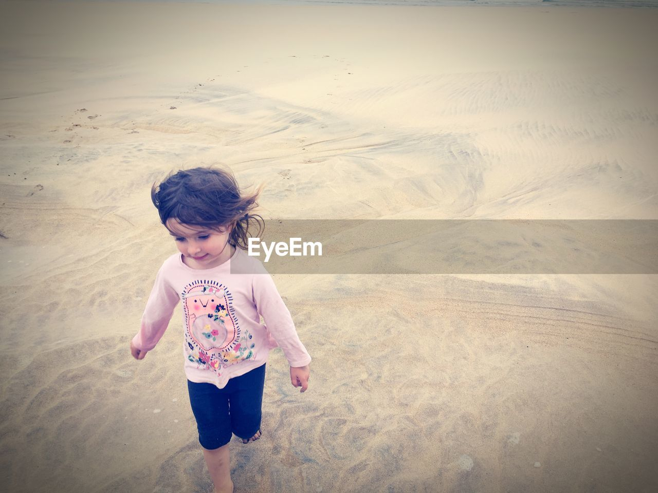 High angle view of girl walking on beach at hayle