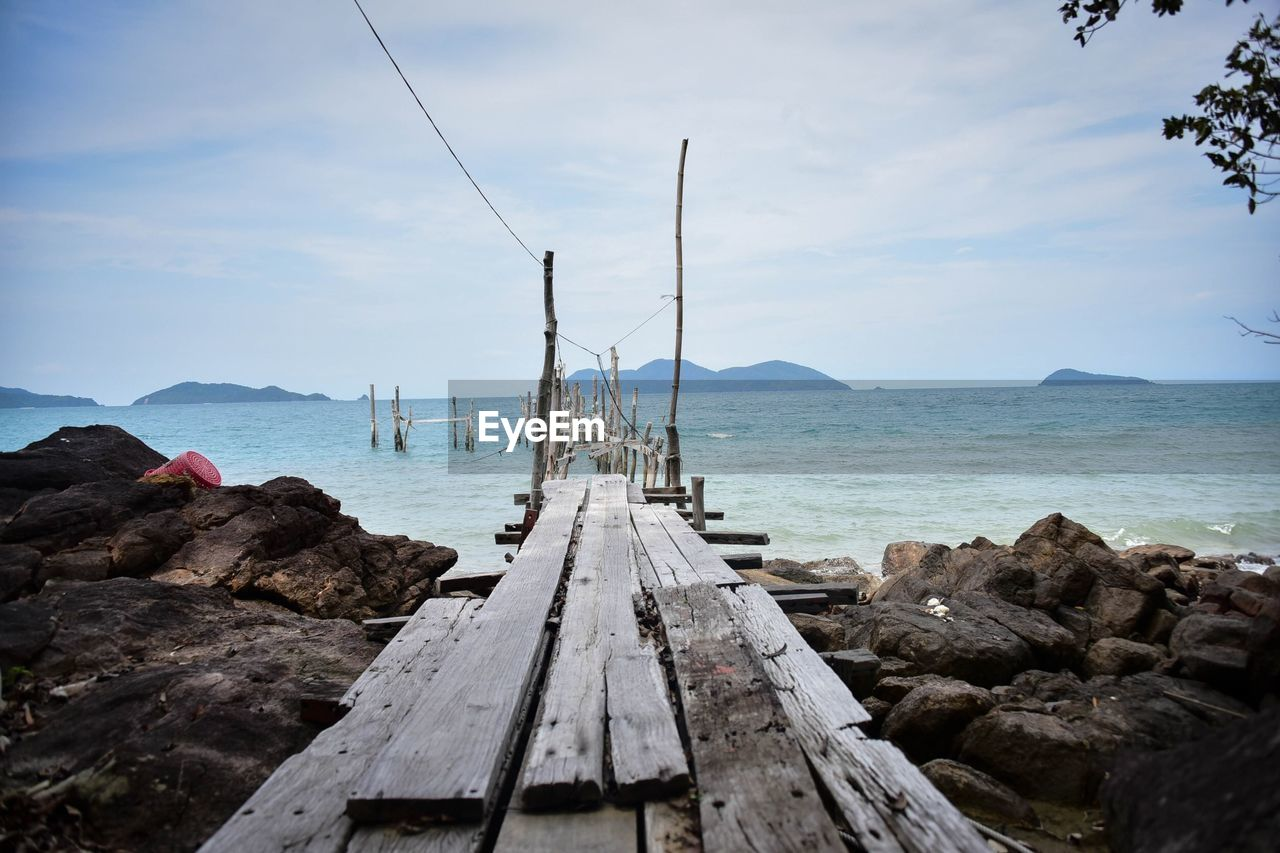 sky, water, sea, nature, rock, rock - object, tranquil scene, wood - material, beauty in nature, no people, scenics - nature, day, tranquility, solid, cloud - sky, direction, horizon, horizon over water, non-urban scene, outdoors, sailboat