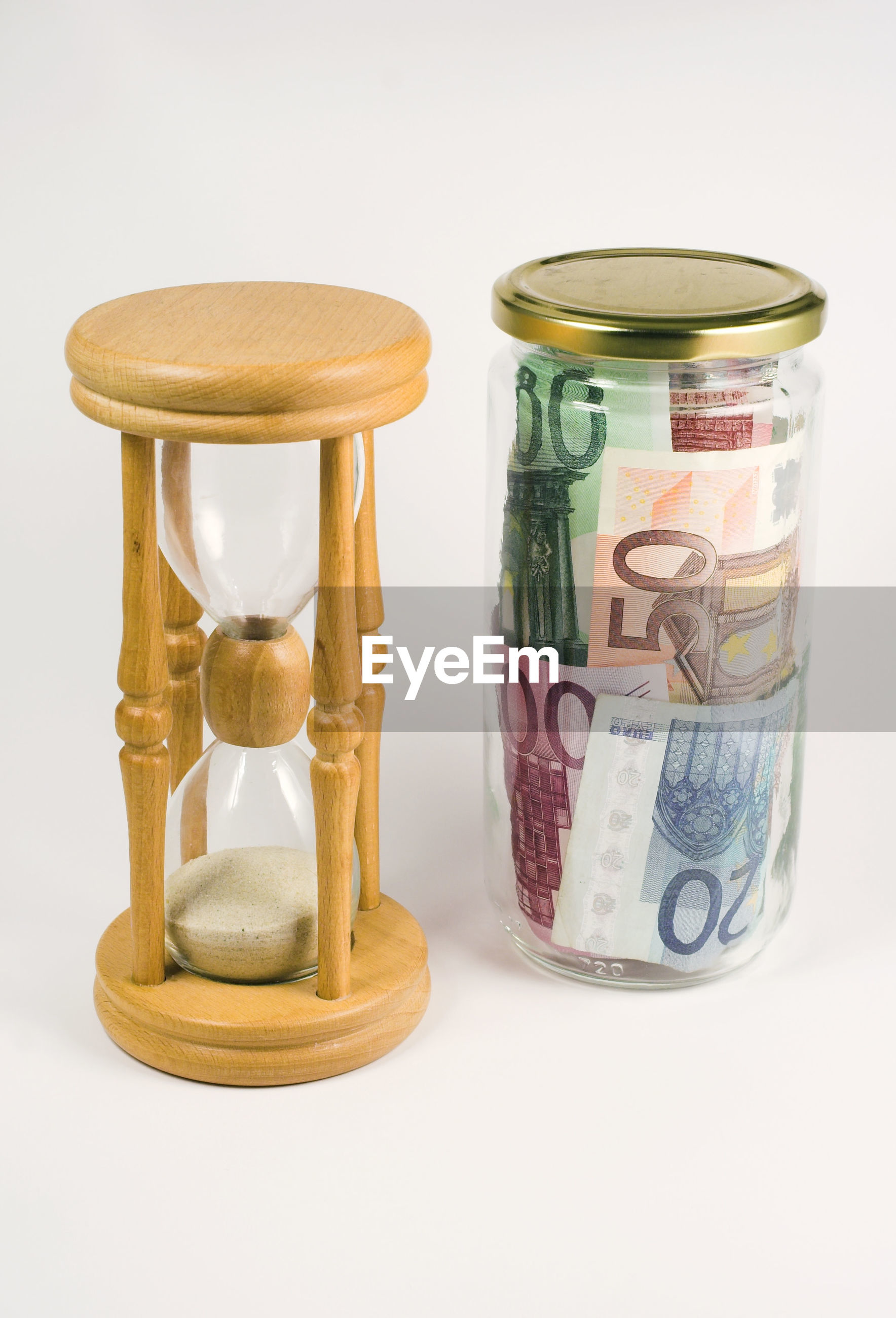 Paper currencies by hourglass in container on white background