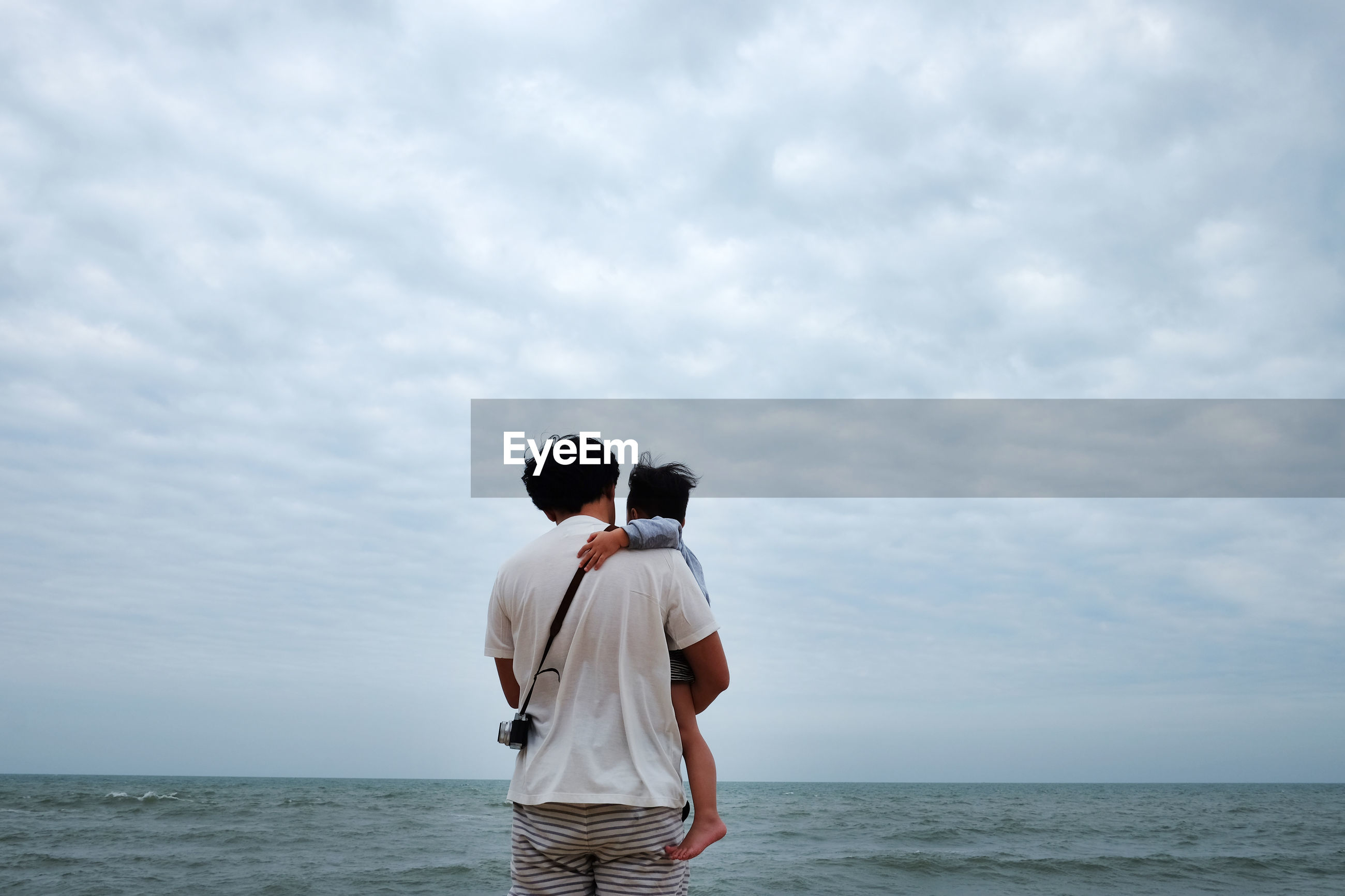 Rear view of father carrying son at beach against cloudy sky