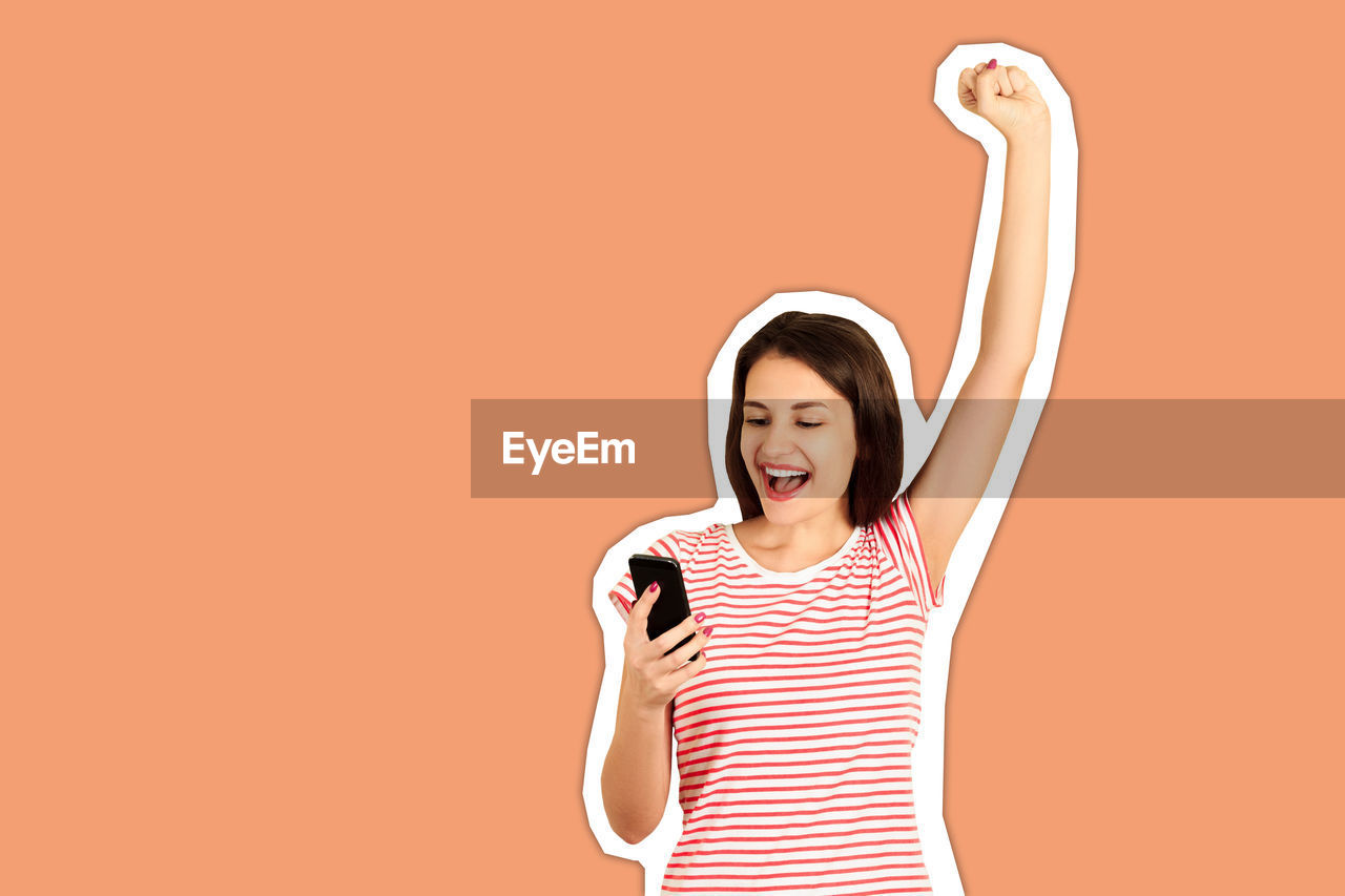 Shocked young woman holding mobile phone cut out against brown background