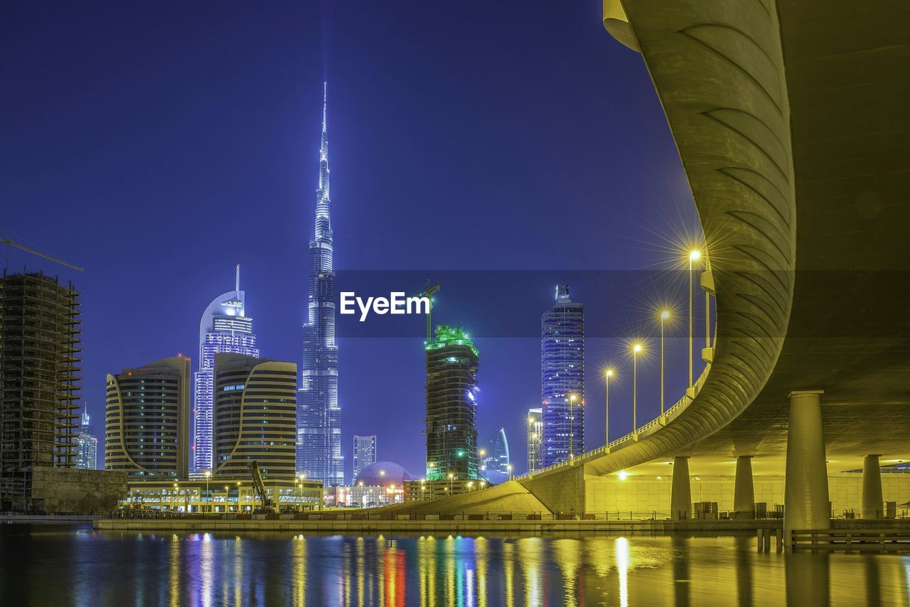 Low Angle View Of Illuminated Burj Khalifa In Front Of River In City At Night