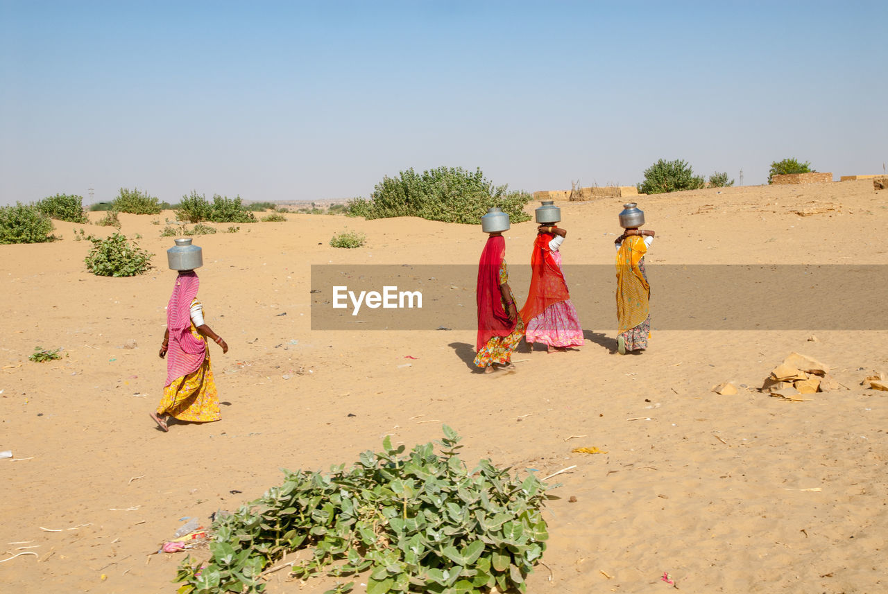 Women Carrying Pots On Head While Walking On Sand At Remote Desert