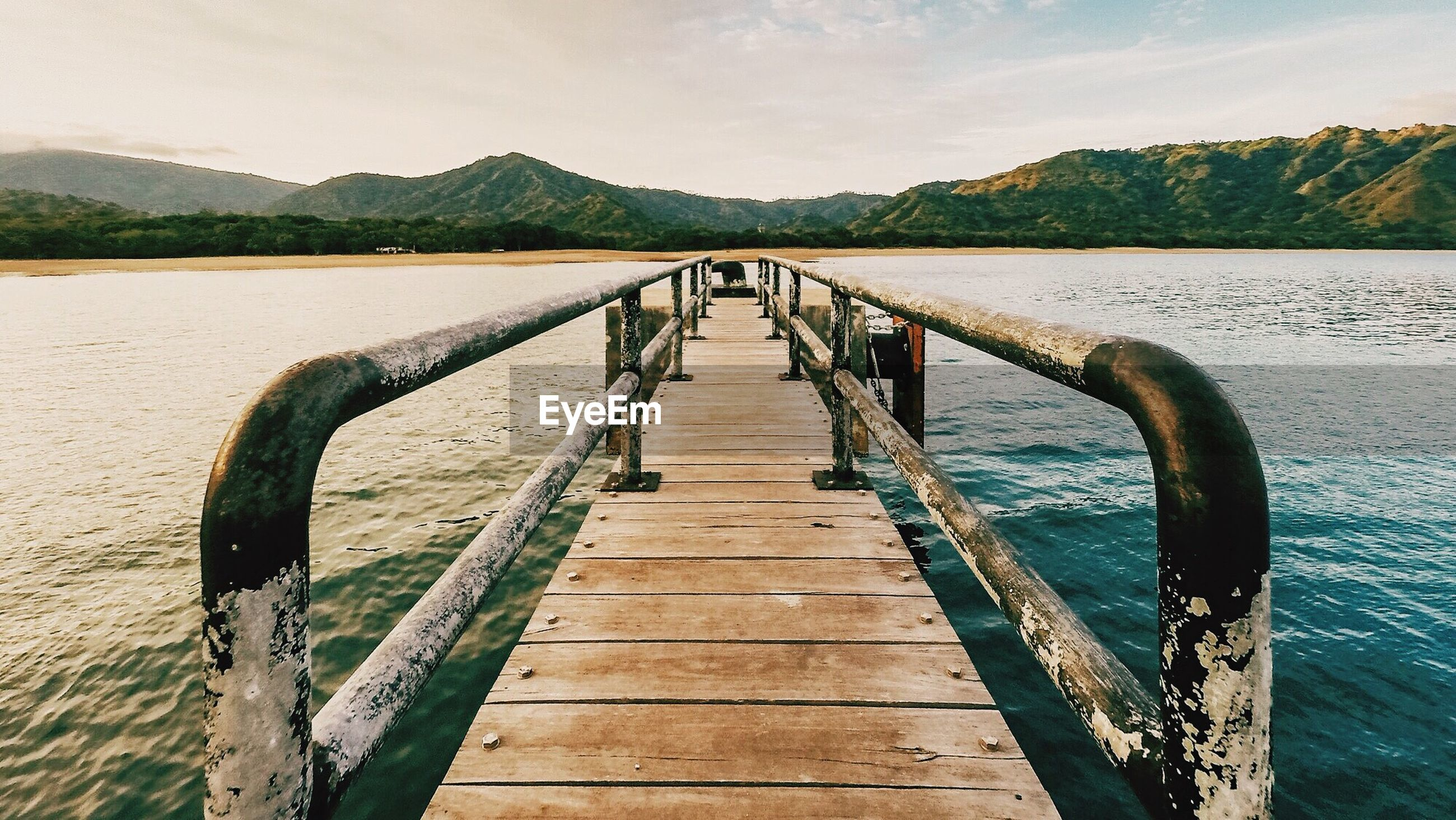Pier over lake in front of mountains against sky
