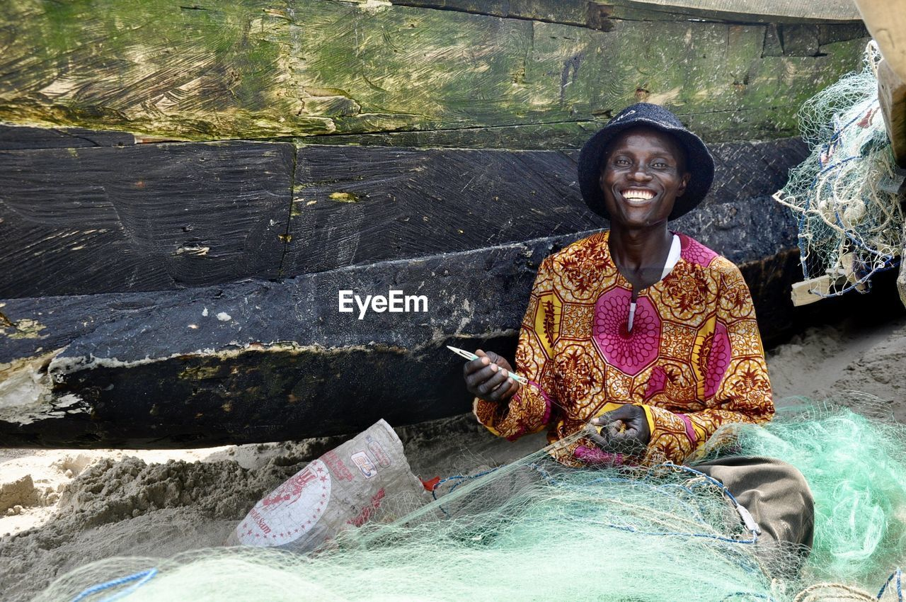 Portrait of cheerful fisherman with net at beach