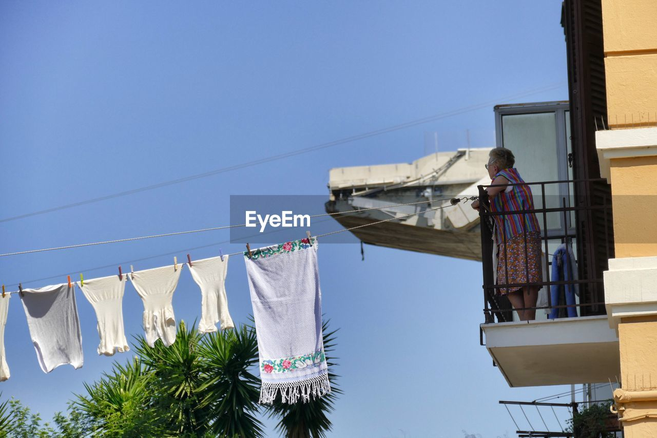 hanging, clothing, laundry, drying, sky, architecture, clothesline, low angle view, nature, building exterior, clear sky, day, built structure, cleaning, sunlight, blue, building, textile, washing, people, outdoors, housework, clean
