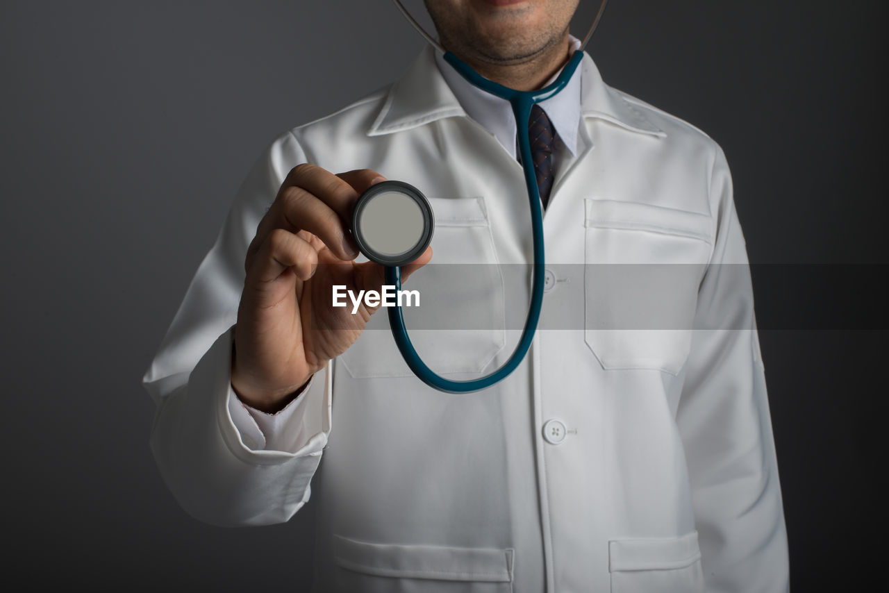 Midsection Of Doctor Holding Stethoscope Over Black Background