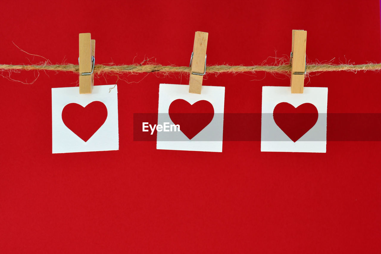 Close-up of heart shapes hanging on red background