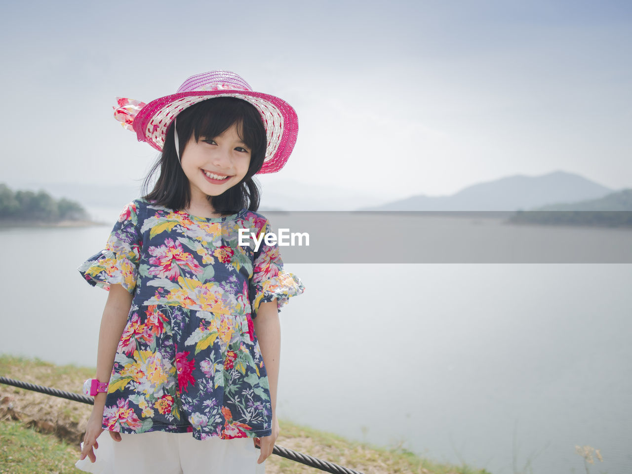 Portrait of smiling girl wearing hat standing by lake