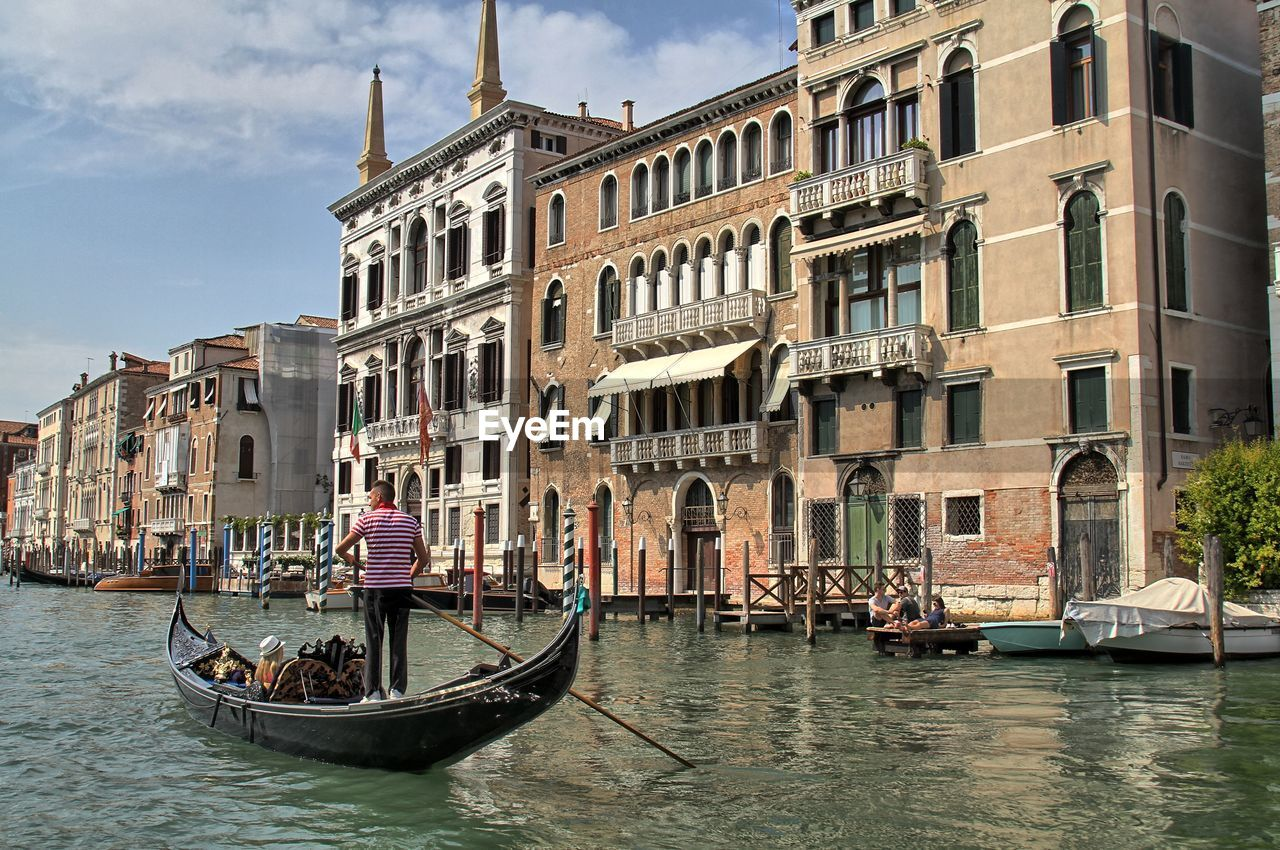architecture, building exterior, gondola - traditional boat, canal, built structure, nautical vessel, tourism, transportation, real people, water, day, outdoors, gondolier, travel destinations, men, sky, one person, city, people