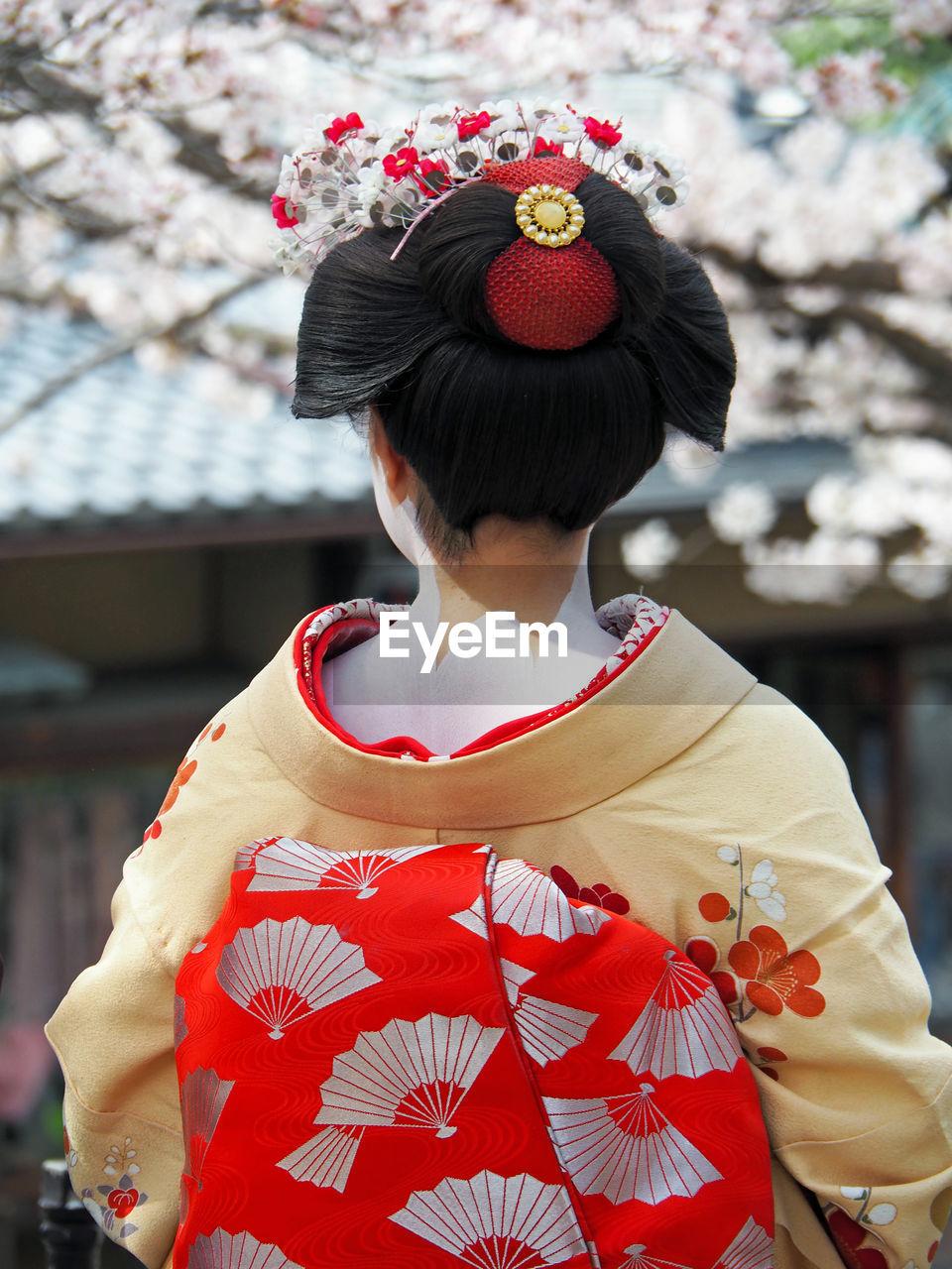 Rear View Of Woman Wearing Kimono Against Cherry Tree